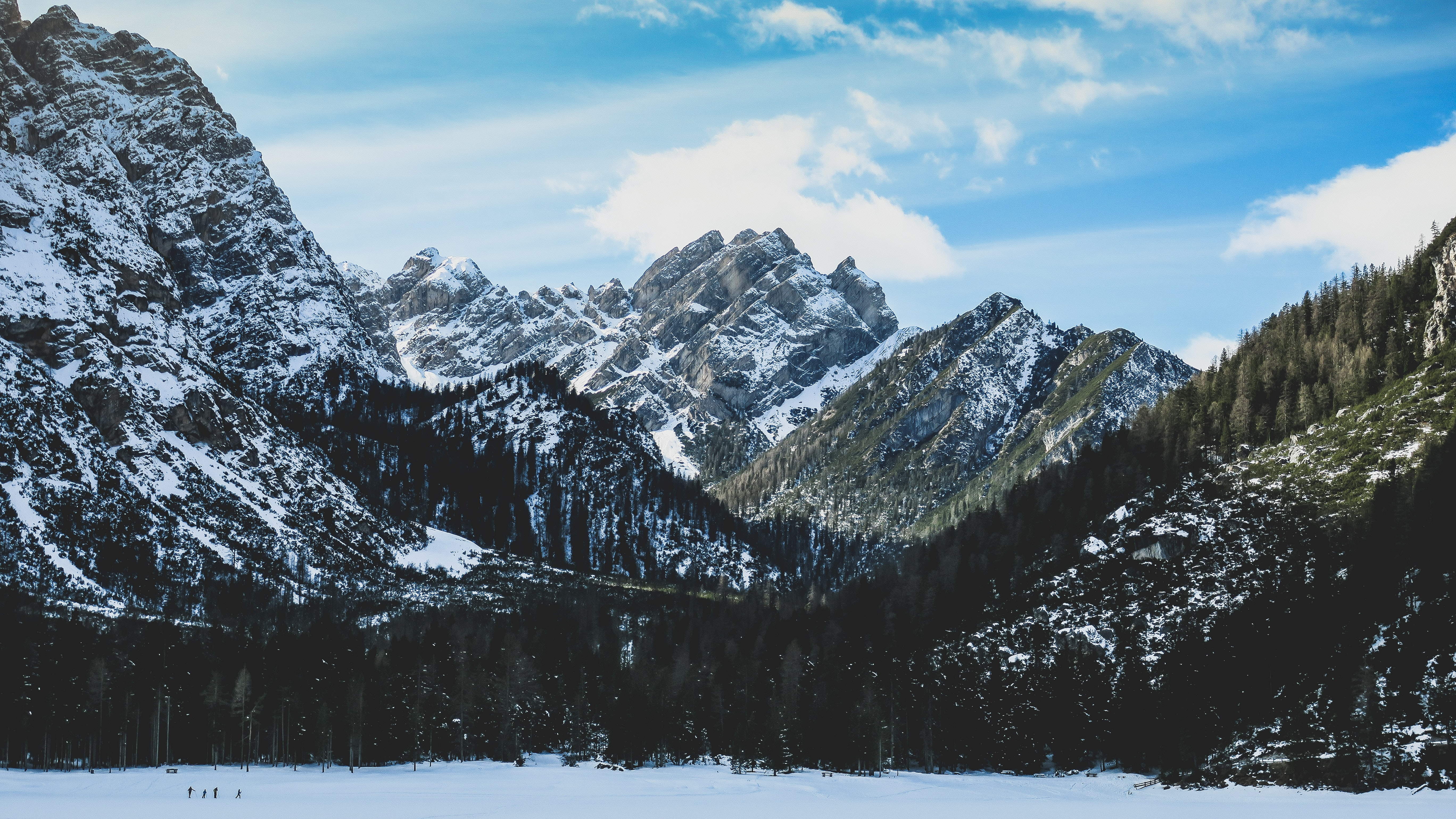 A wintry scenery with craggy mountain crests and wooded slopes near Lago di Braies
