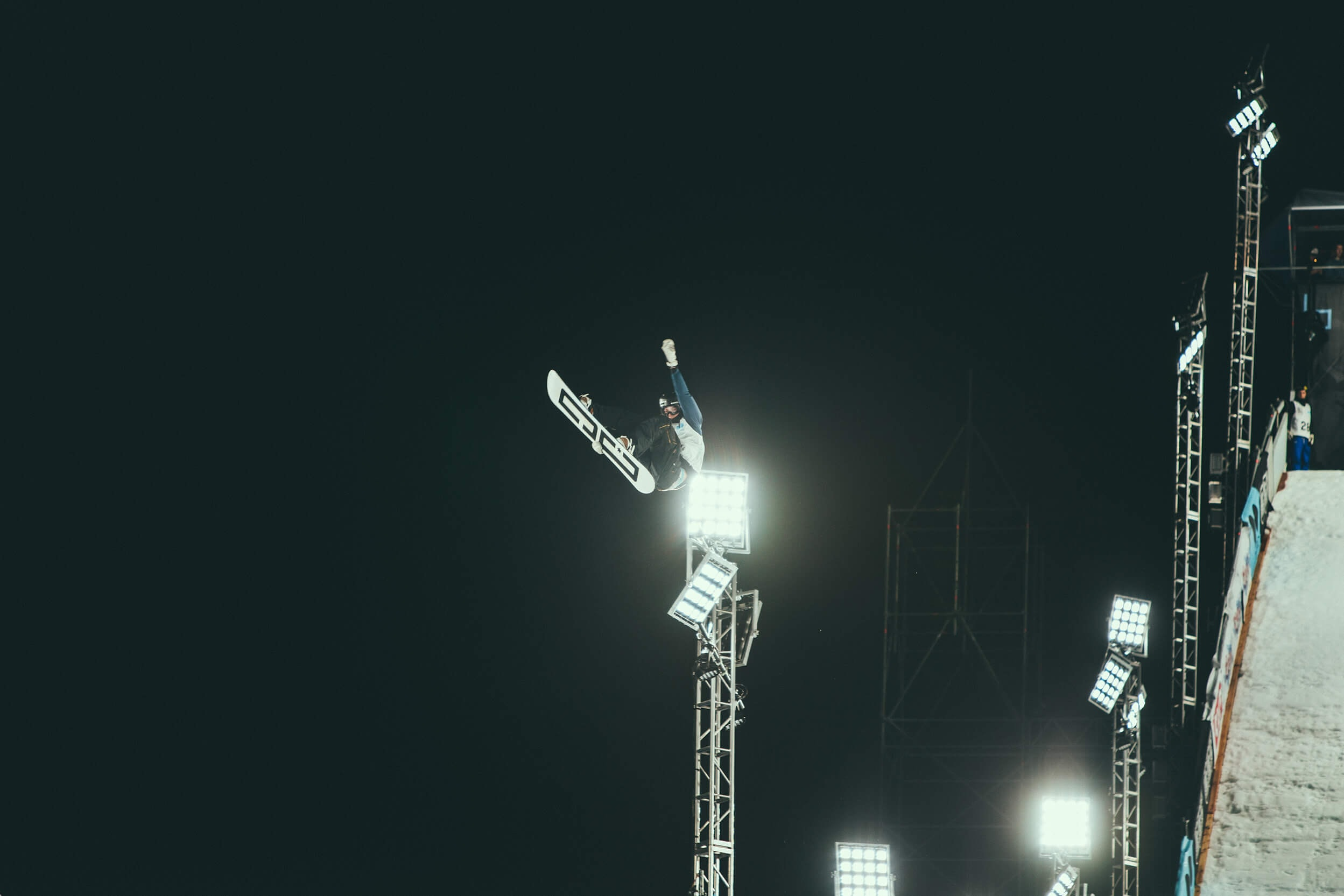 person snowboarding making stunts during nighttime