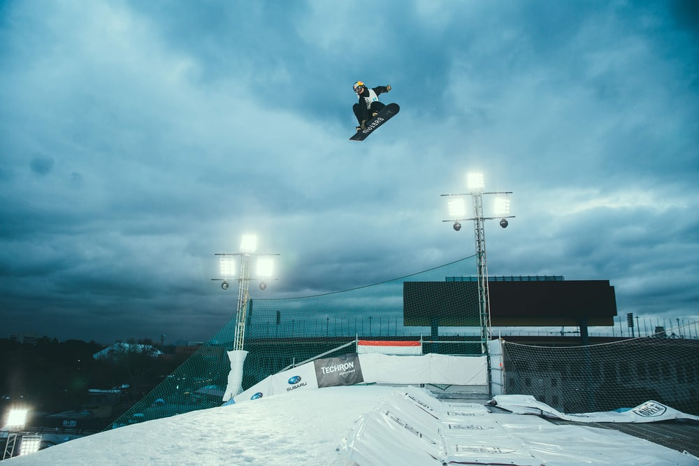 person snowboarding in mid air under cloudy sky