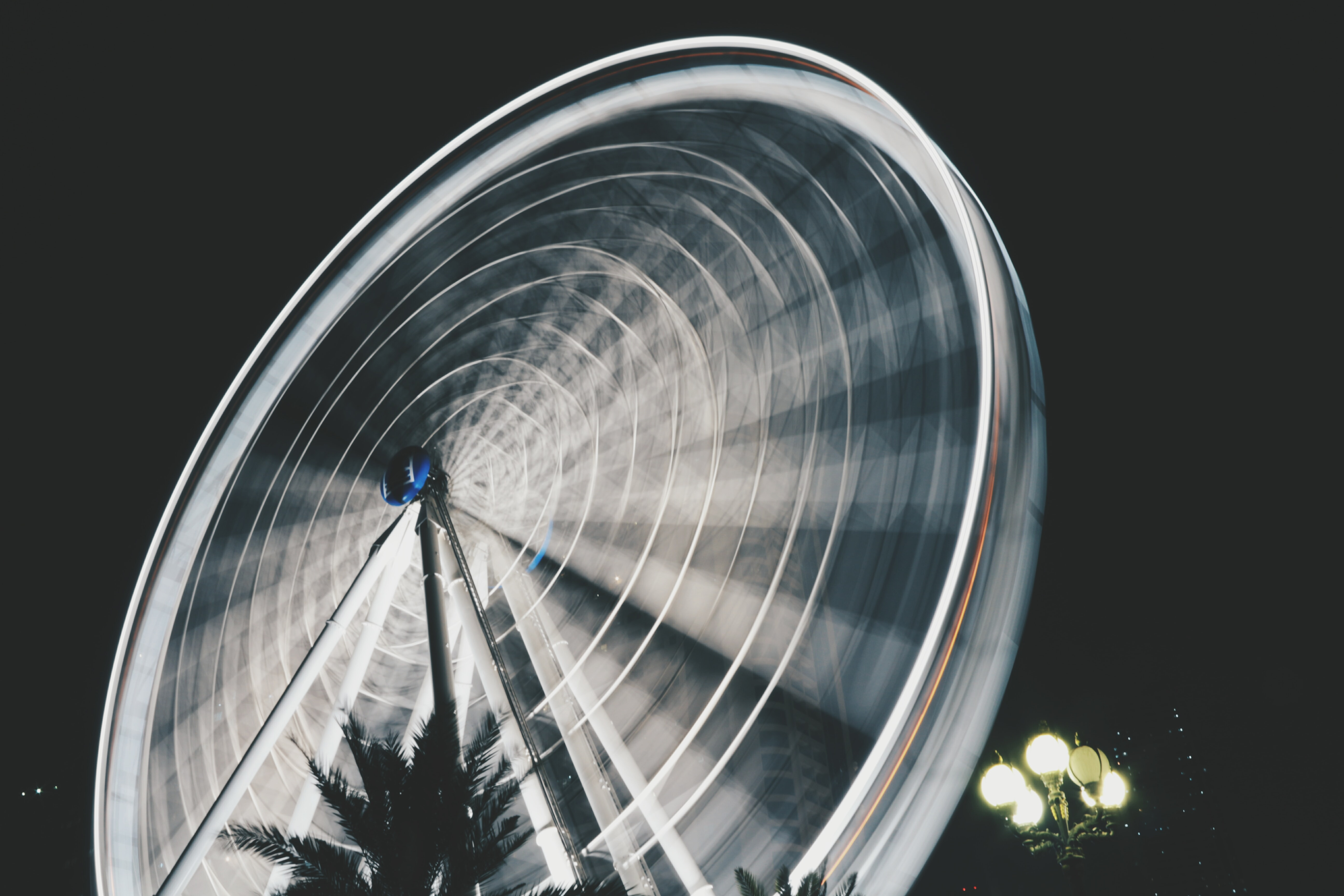 An illuminated ferris wheel in Al Qasba in motion with timelapsed light trails