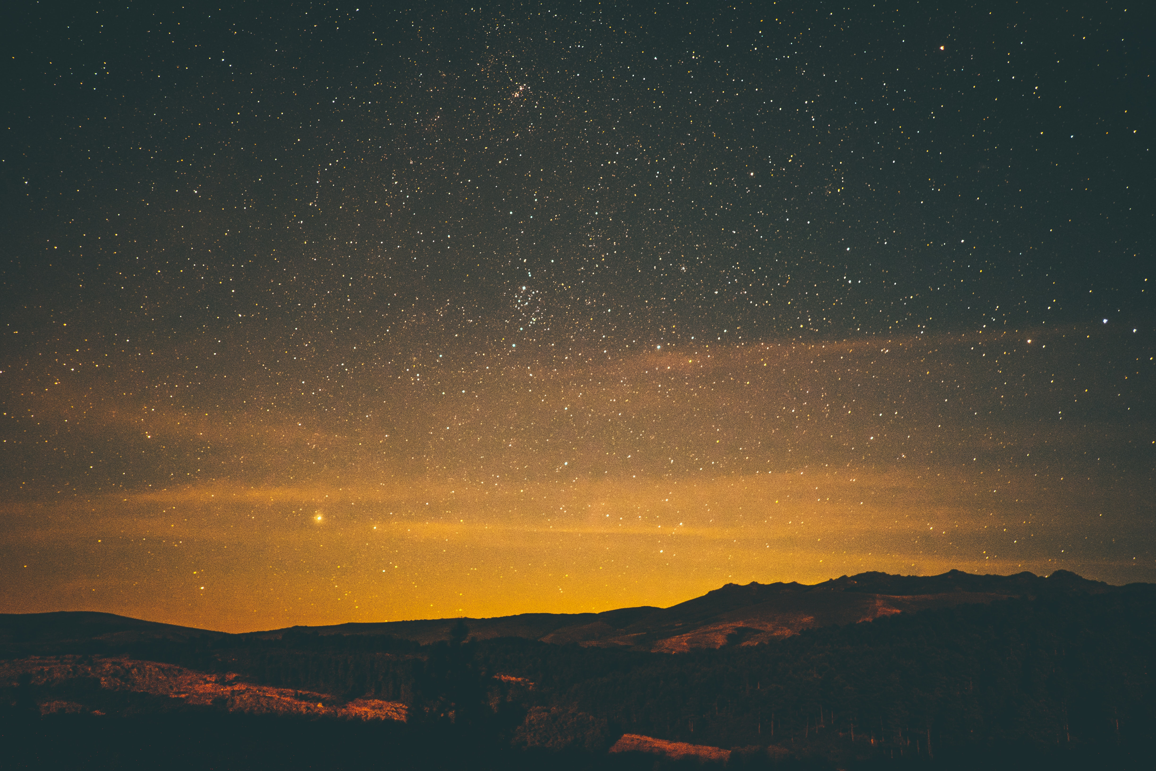 A golden sunset fades into a dark starry night sky over some mountains