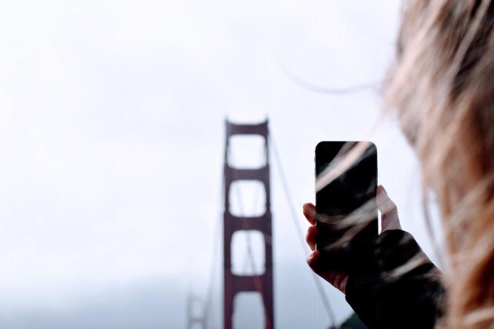 person taking a photo of Golden Gate bridge