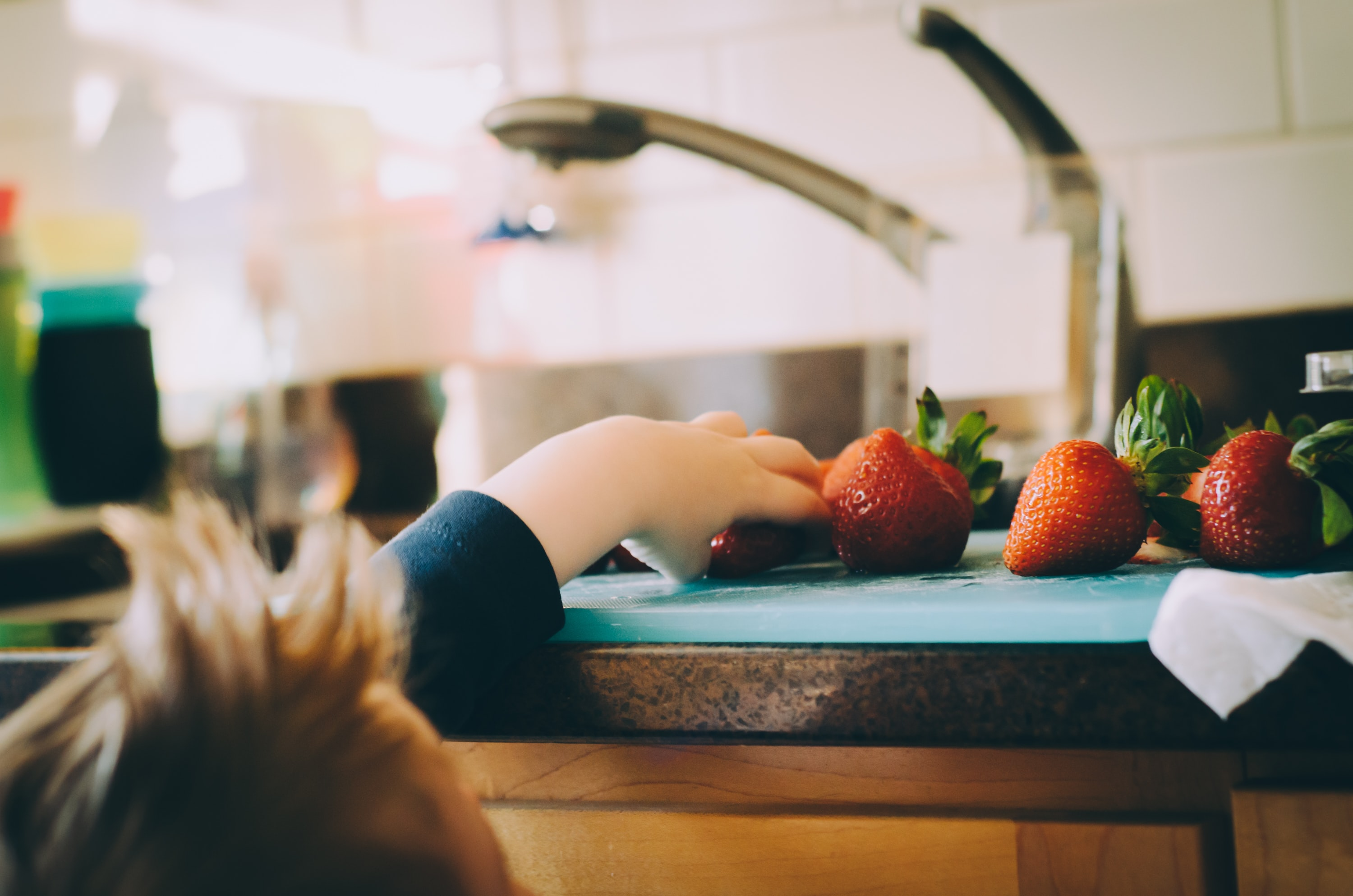 A little boy taking strawberries off of a cutting board on the countertop