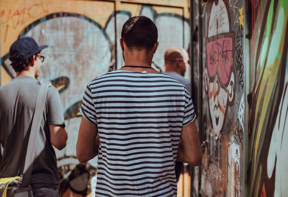 man wearing black and white stripe standing near graffiti
