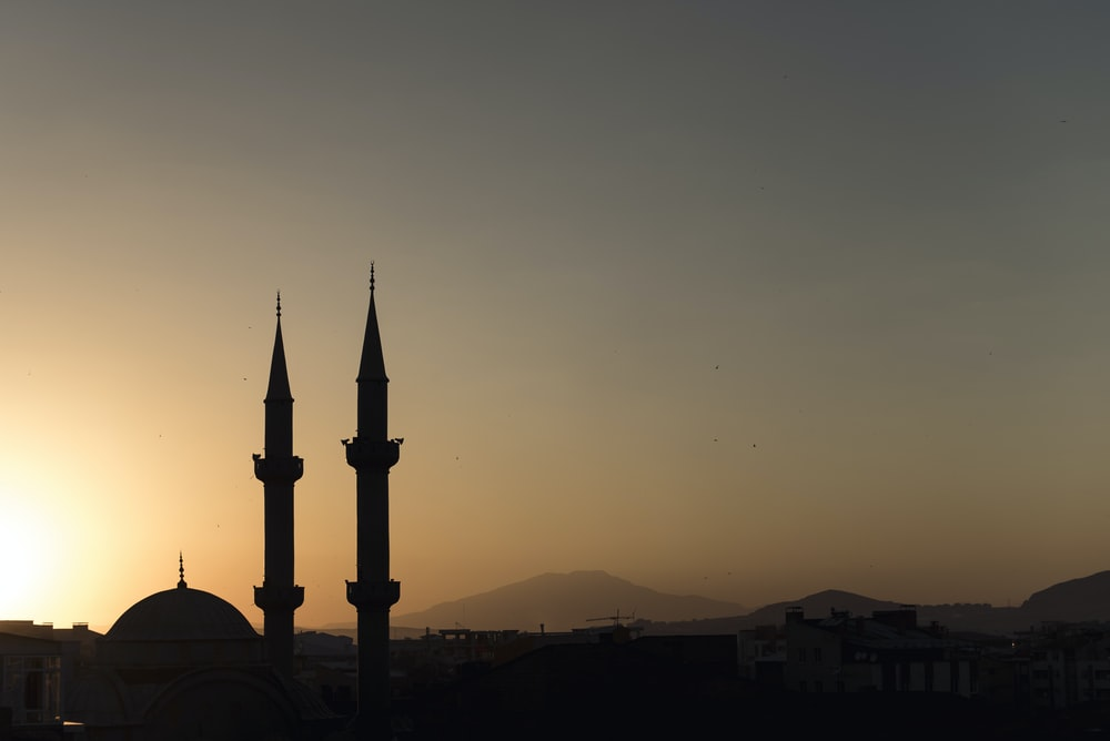 two mosque minarets under calm sky