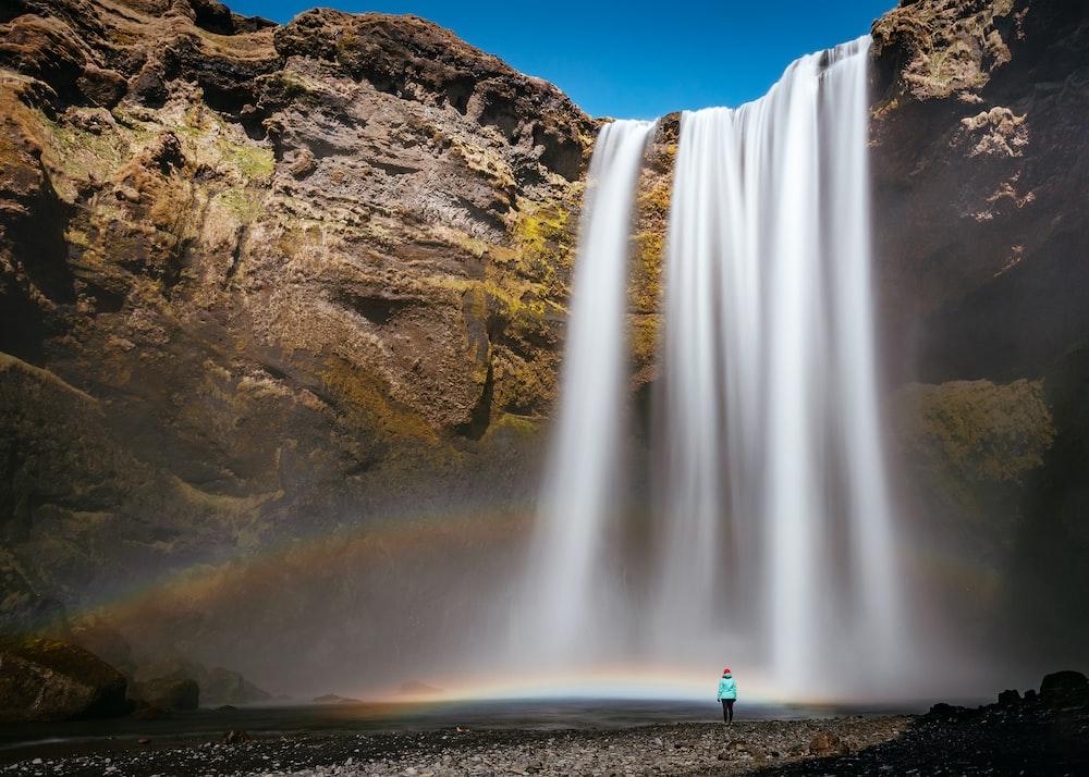person walking beside waterfall