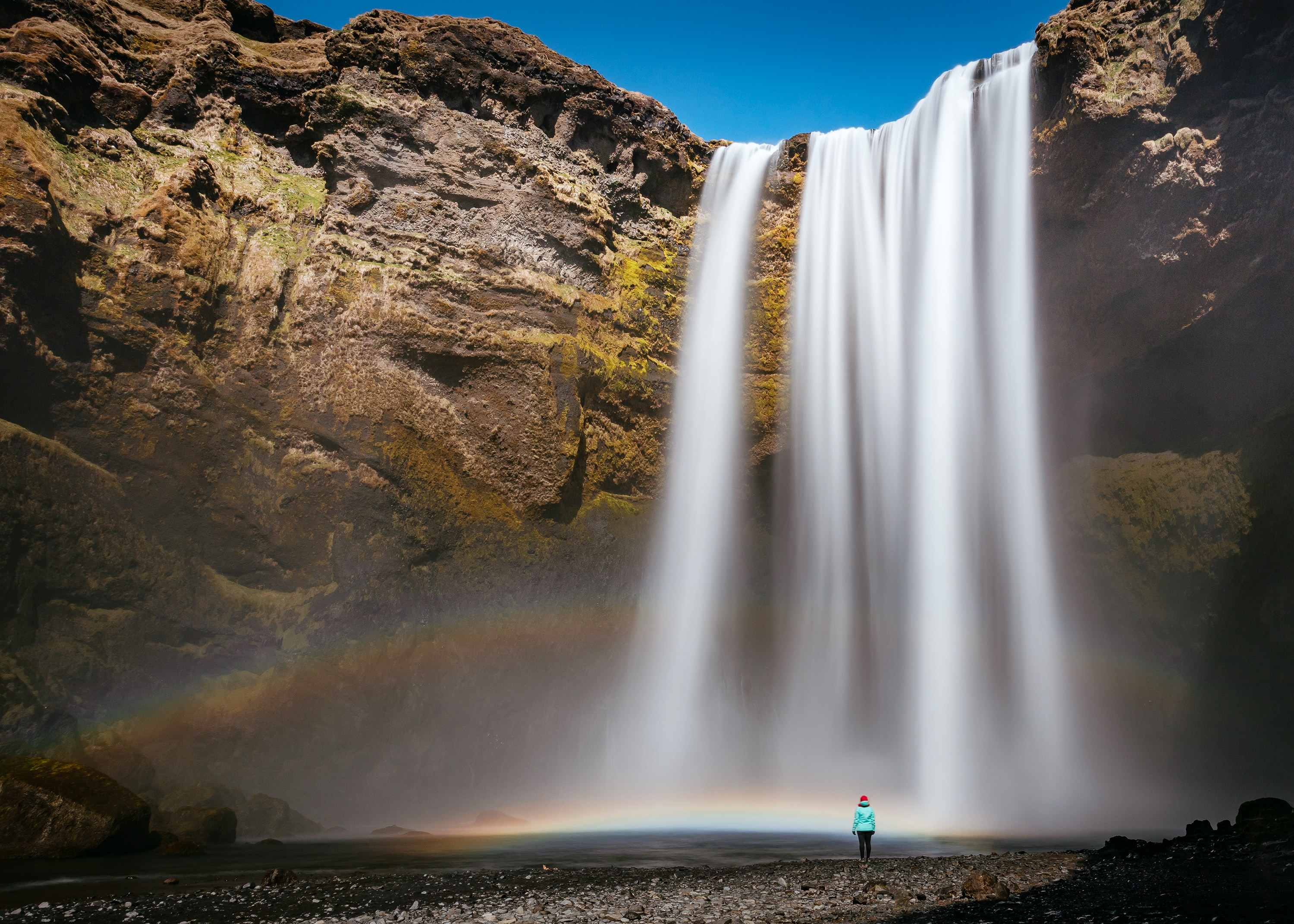 person walking beside waterfall