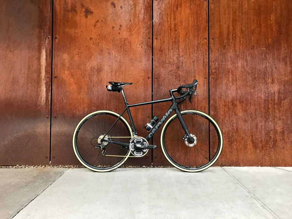 black road bike parked beside brown wooden wall