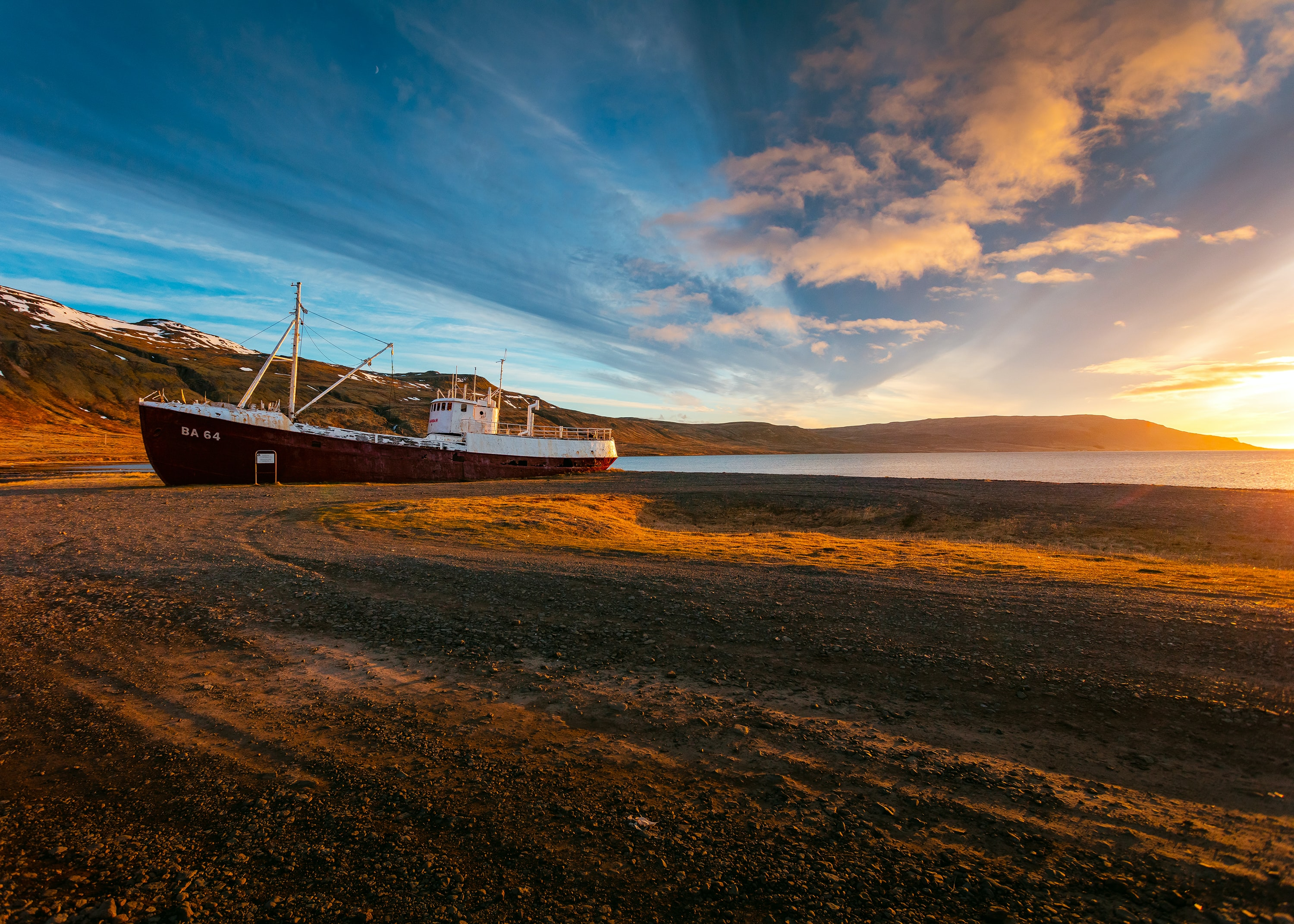 Moored ship on the sand beach at sunset