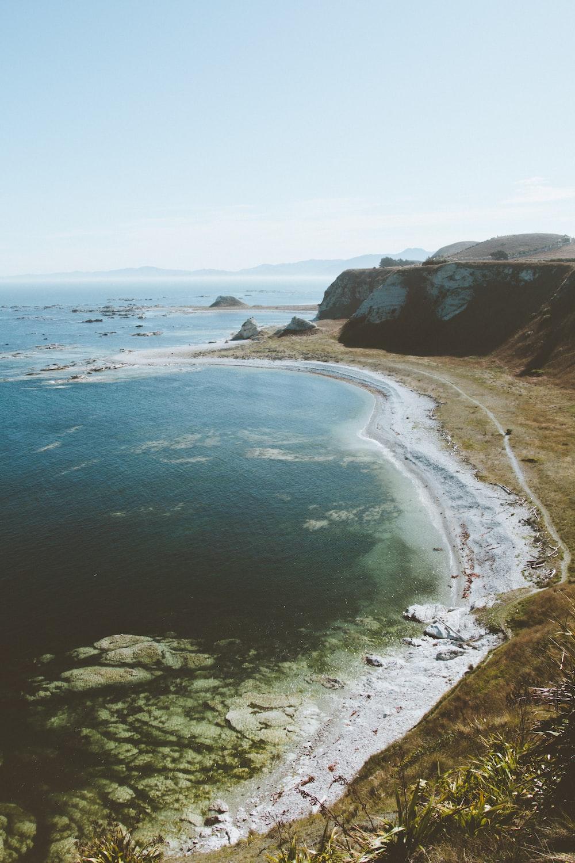 ocean waves beside brown mountain