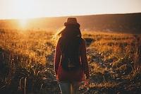 woman walking on grass plains during sunset