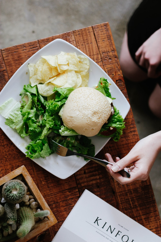 булочка, салат и чипсы подаются на белой керамической тарелке