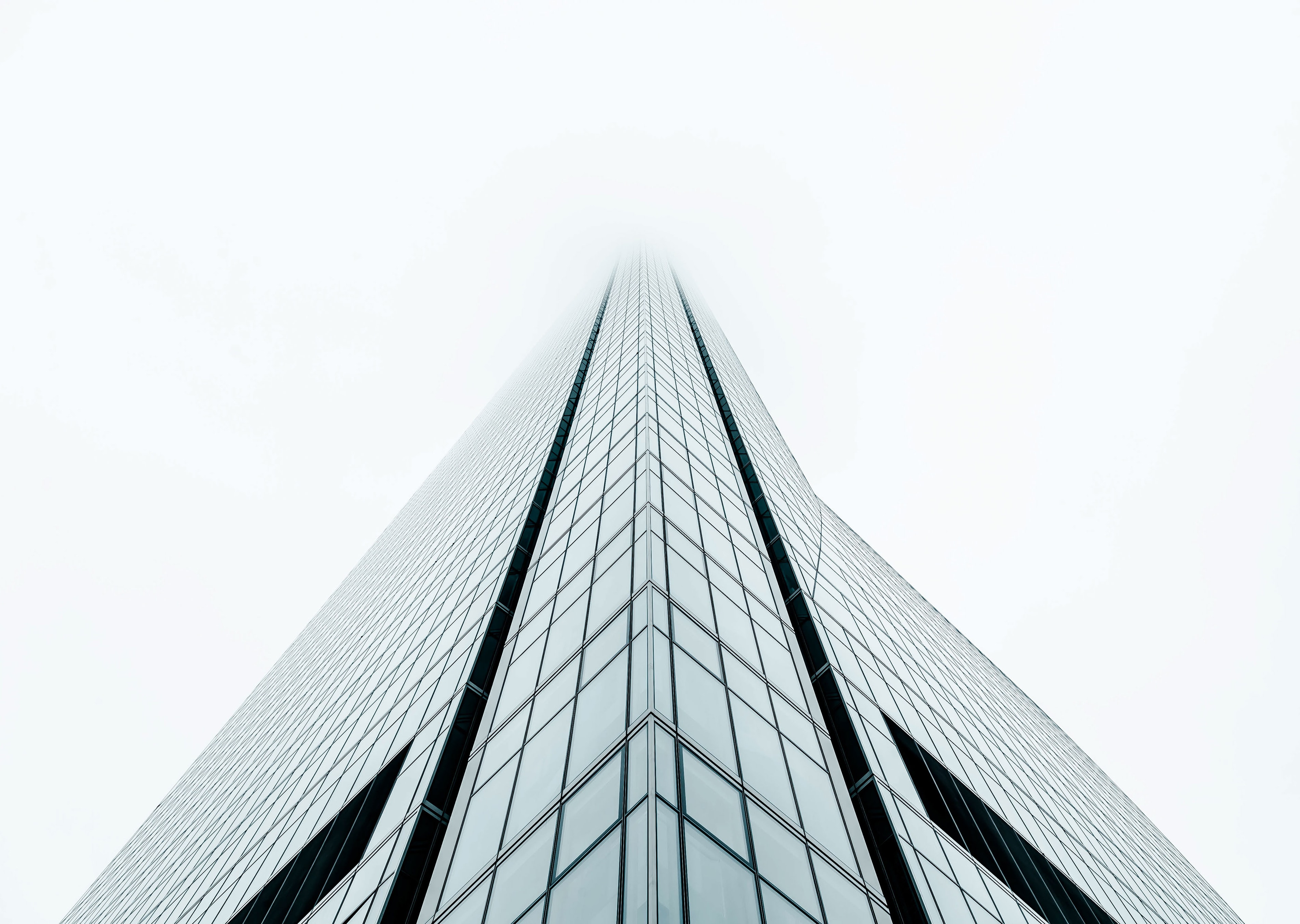 Fog covers the top of a tall building with rectangular glass design facade in Madrid.