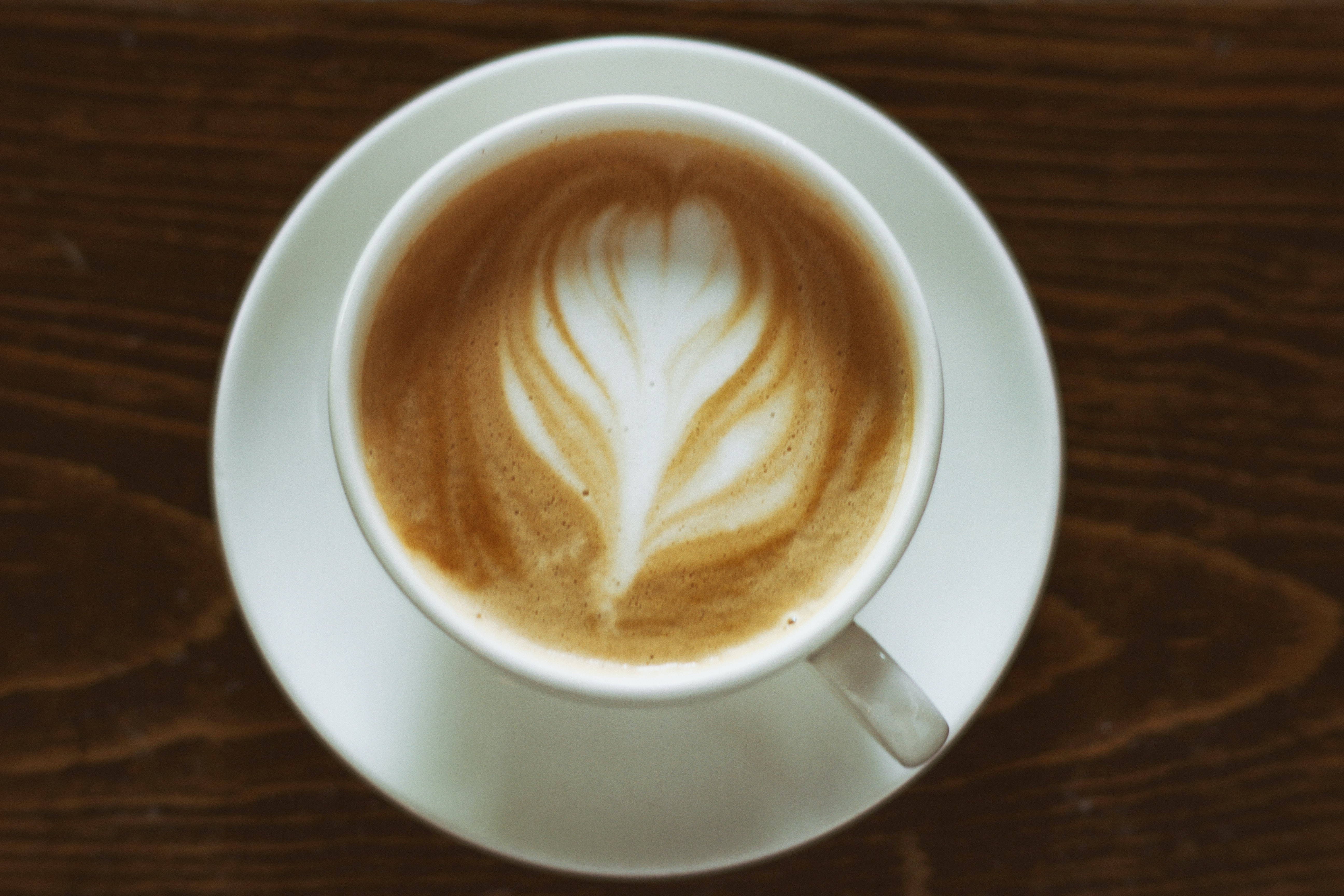 A flower shape on top of a cup of coffee.