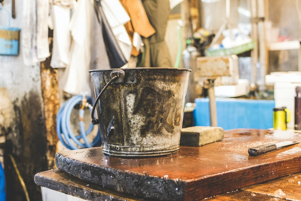 gray bucket on wooden table