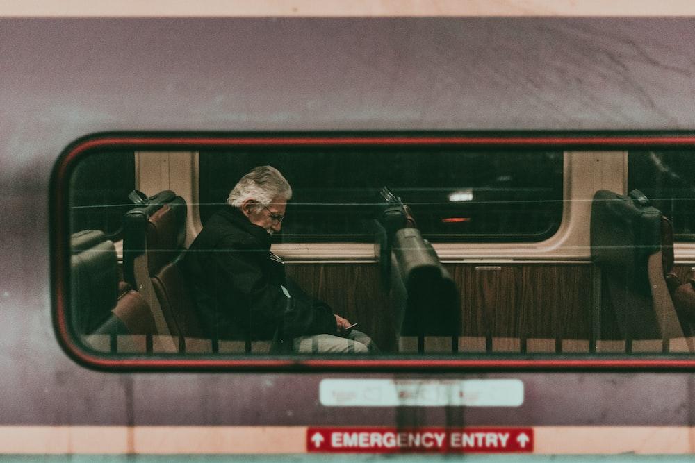 man sitting on train seat