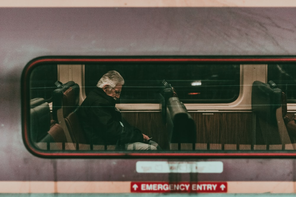 man sitting on train seat
