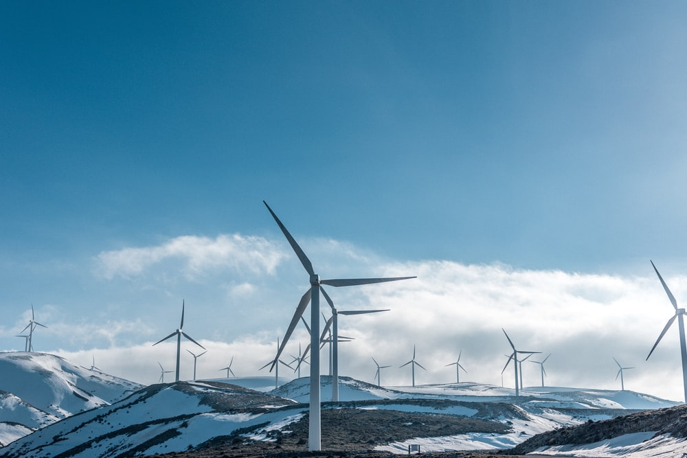wind turbines on snowy mountain under clear blue sky during daytime