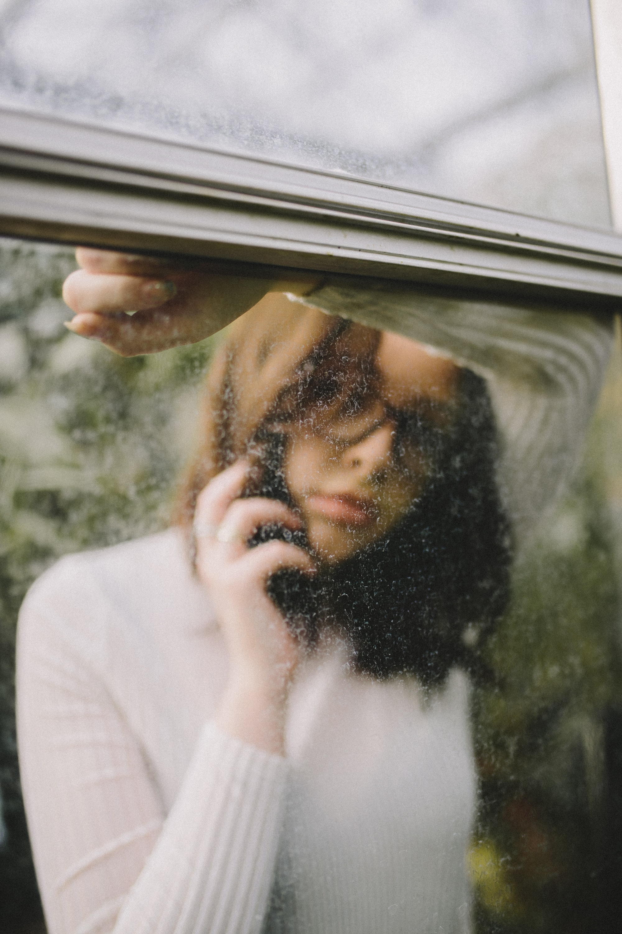 Reflection of a woman leaning against a car window holding a phone