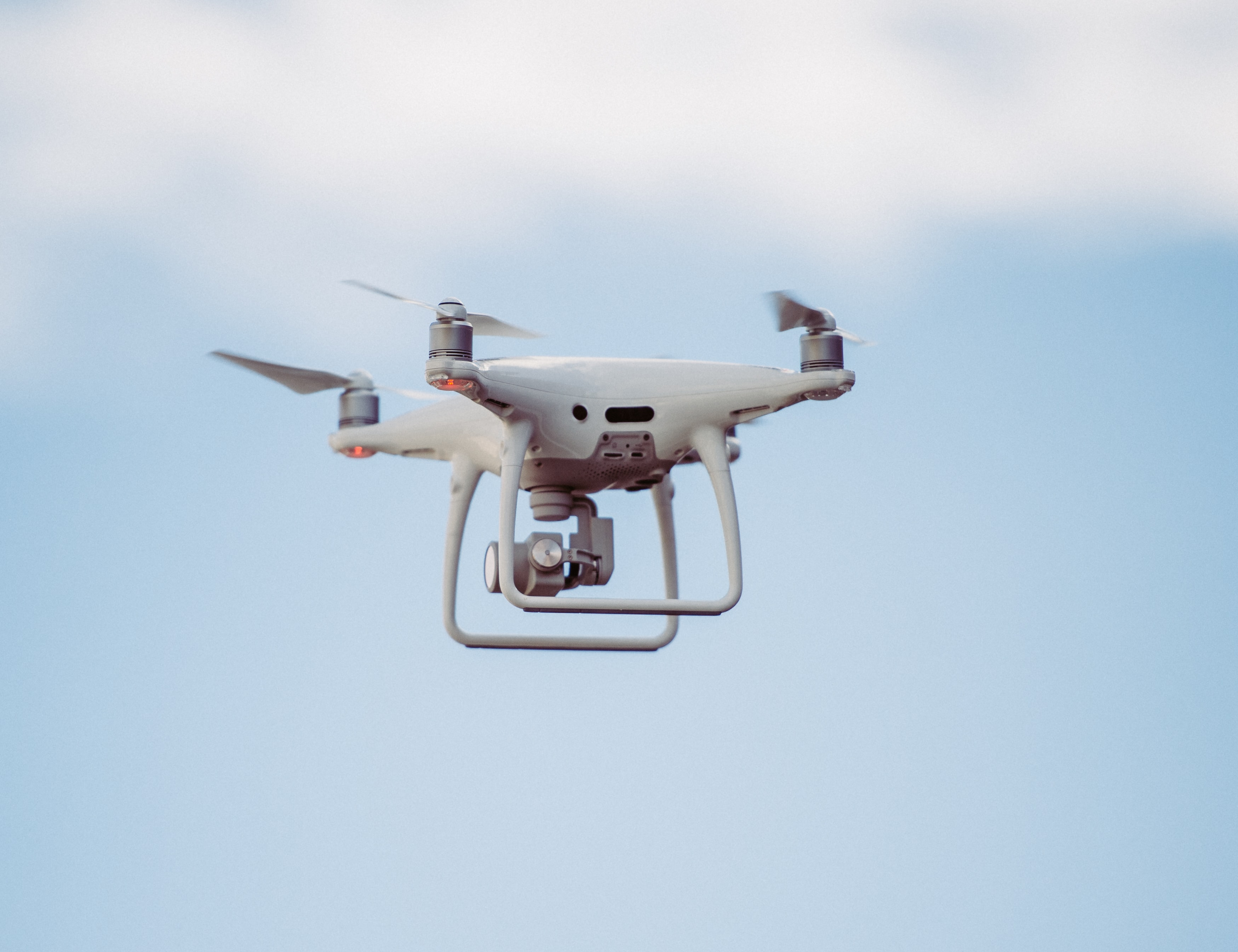 A white DJI drone in the air