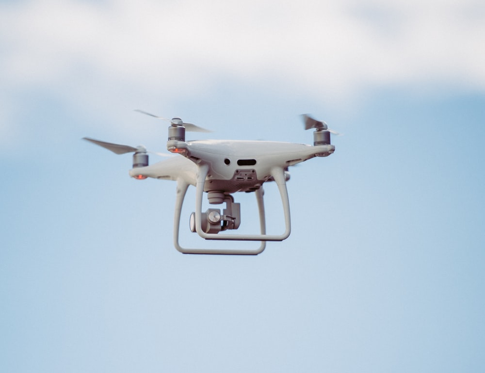 white DJI drone in mid air