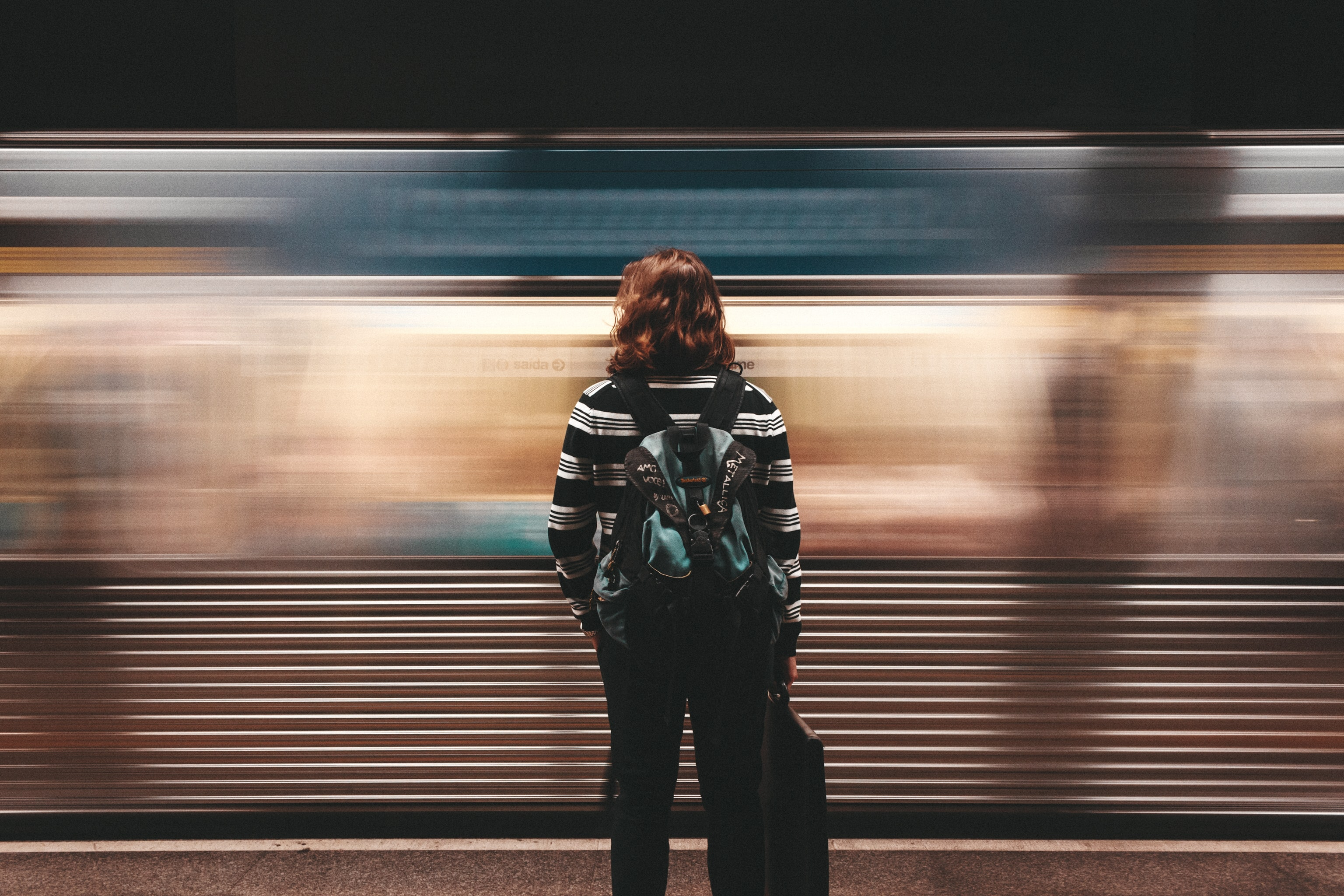A woman watching a blurry train pass by via long exposure photography in São Paulo
