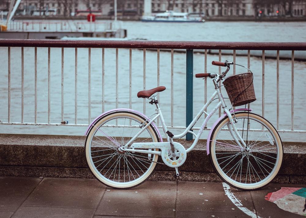 white city bike with basket parked near rails