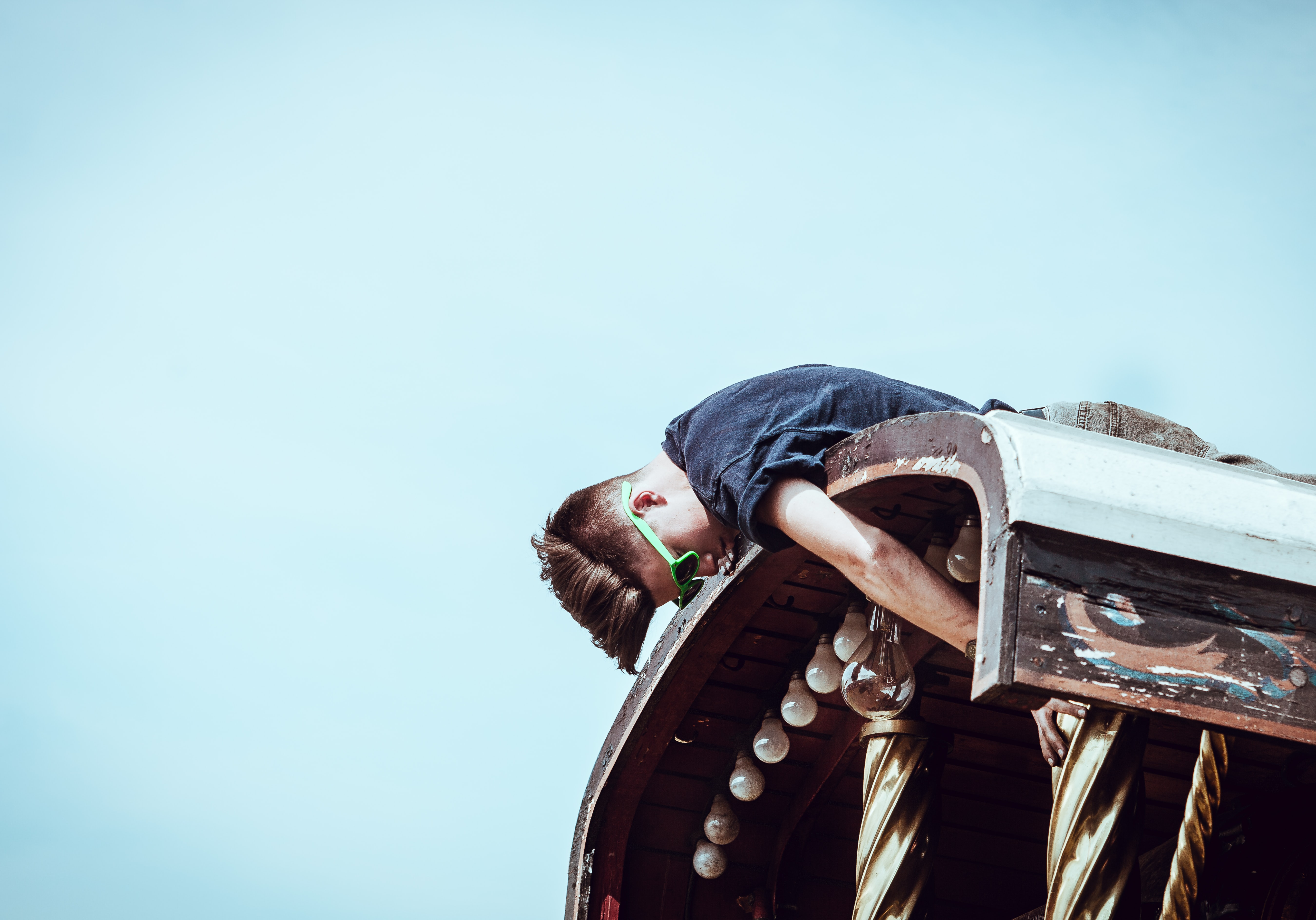 A person lays atop a structure, reaching down to repair lightbulbs against a blue sky