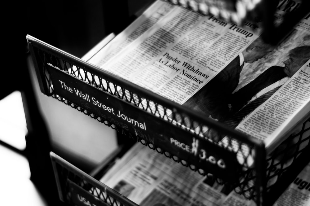 A Black And White Shot Of Newspapers In Store