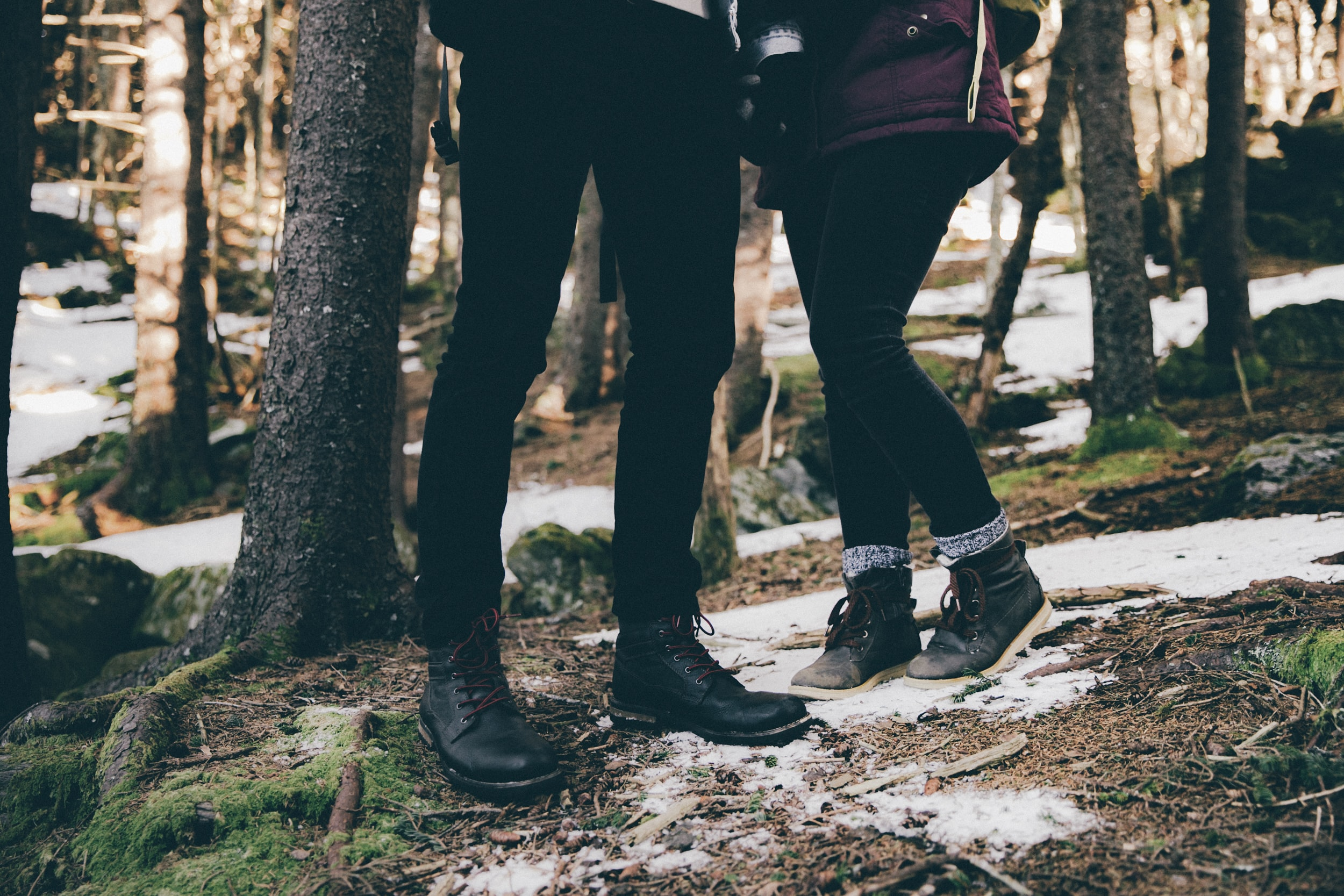 A low shot of a man and a woman standing close to each other in a forest on a winter's day