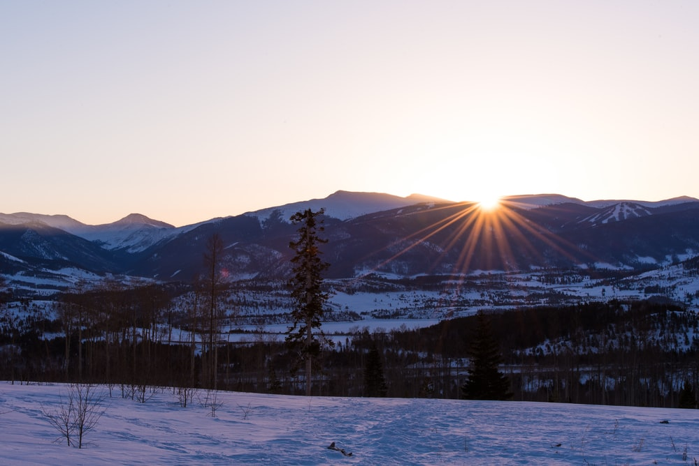 snow-covered mountains near plain area at sunset