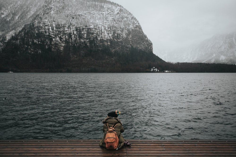 person sitting on wooden dock in front of body of water