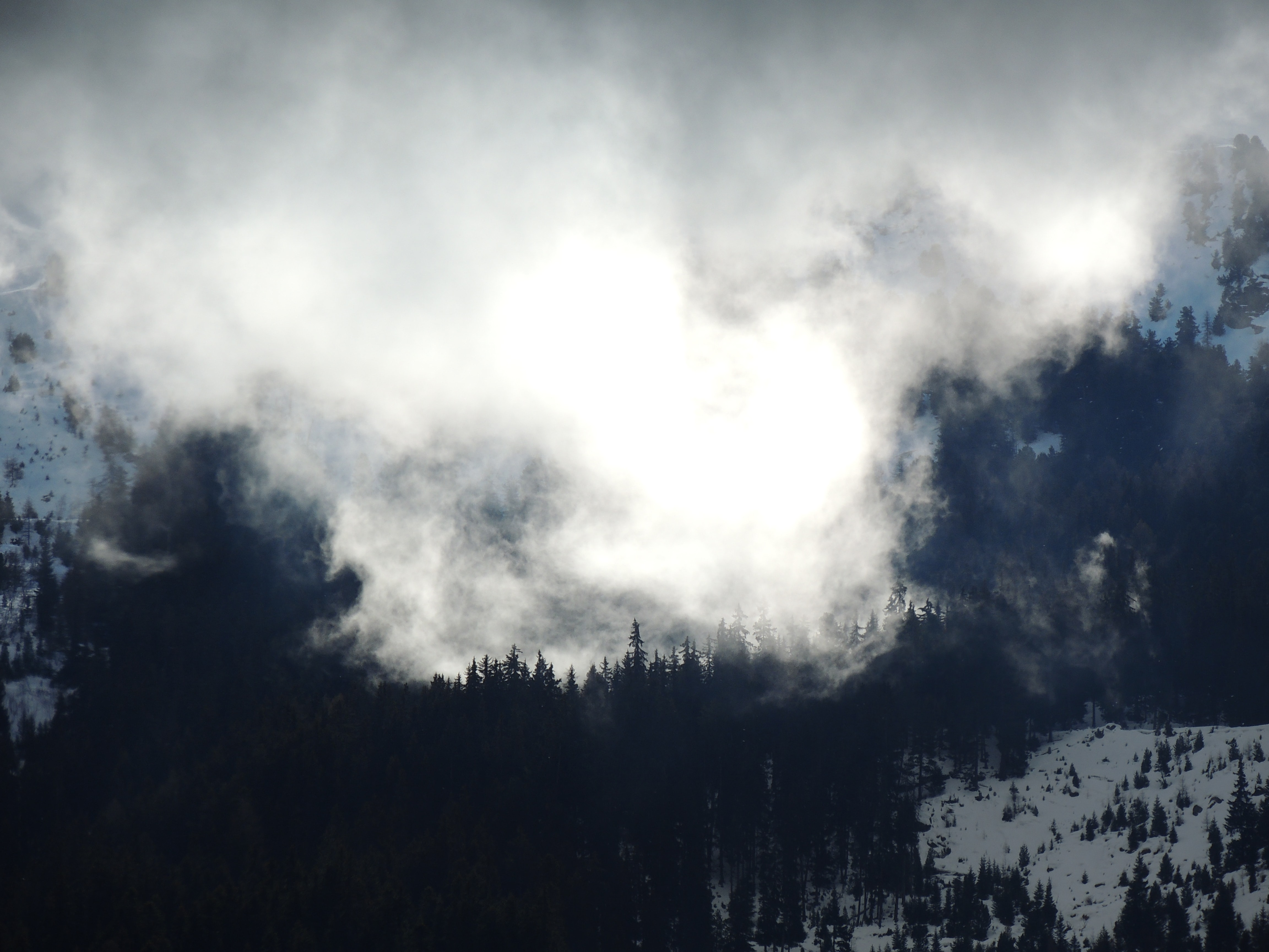 Thick mist obscuring the view on a snowy mountainous landscape in Modane
