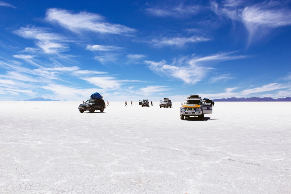 sports utility vehicles on desert under cloudy blue sky during daytime