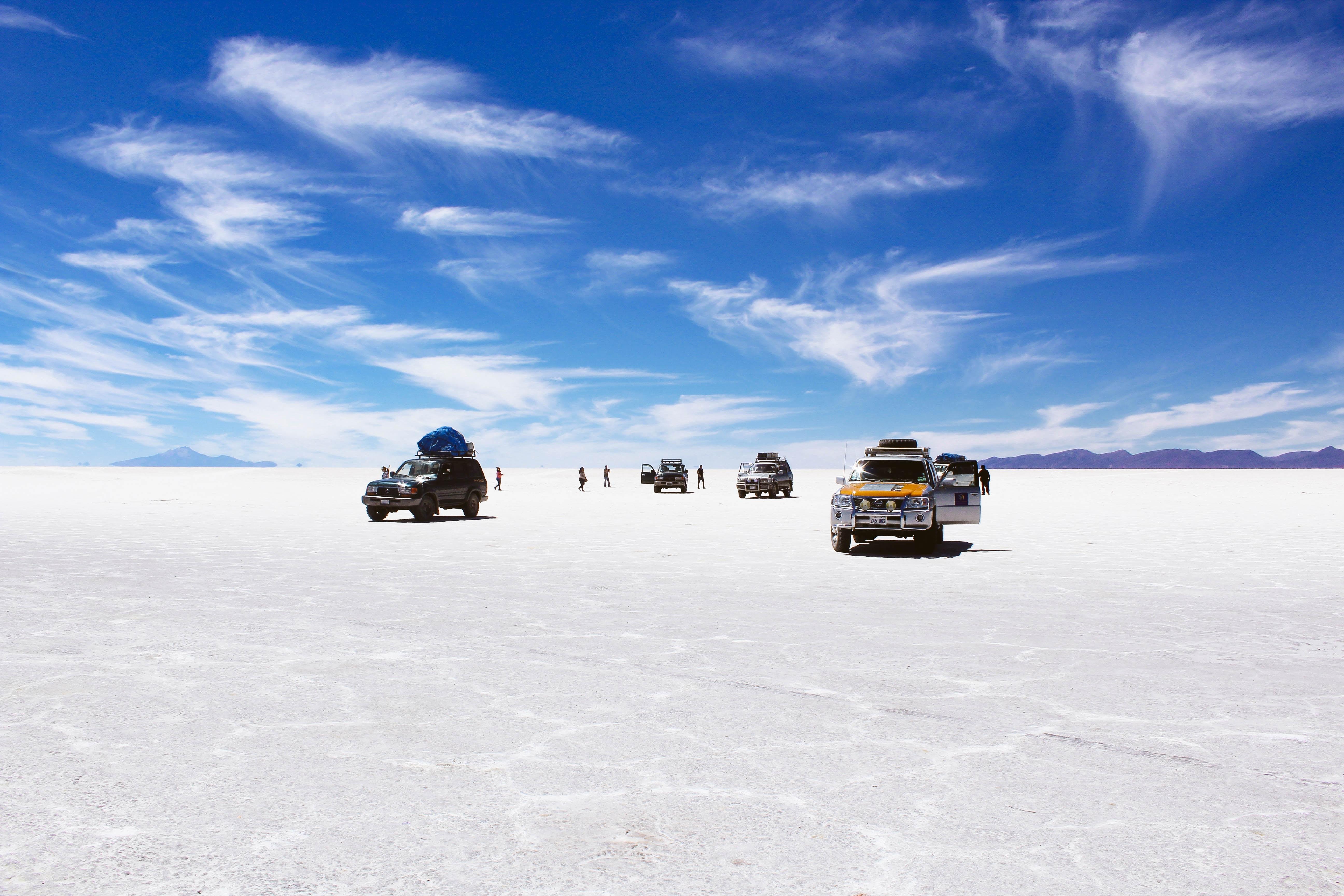 Jeep trucks parked on deserted salt flats of Salar de Uyuni