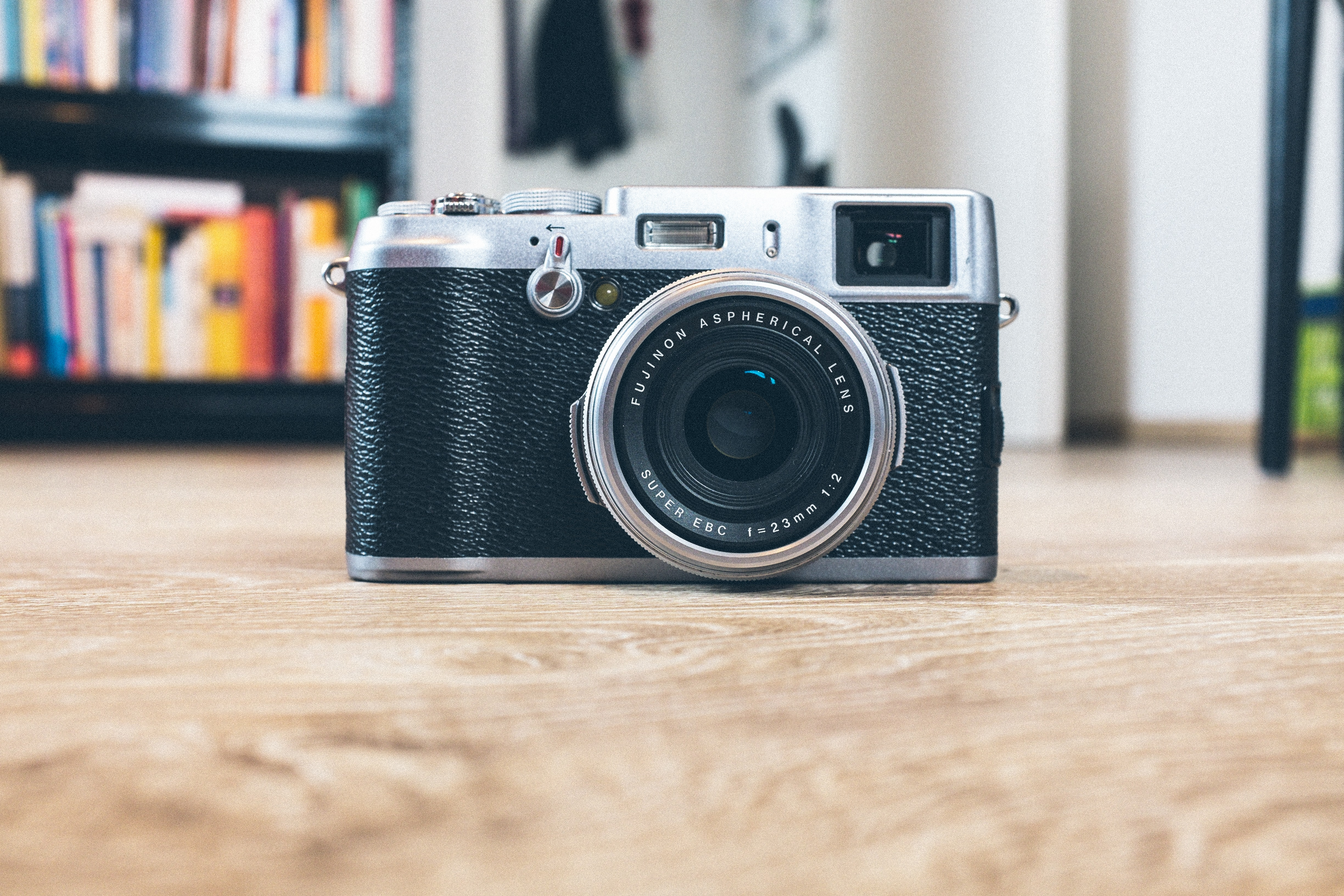 A Fujifilm vintage camera on a wooden floor beside a bookcase