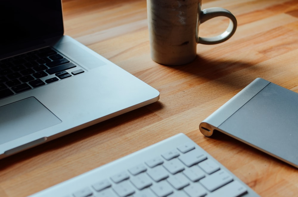 A Keyboard And Mug Next To Laptop On Wooden Surface