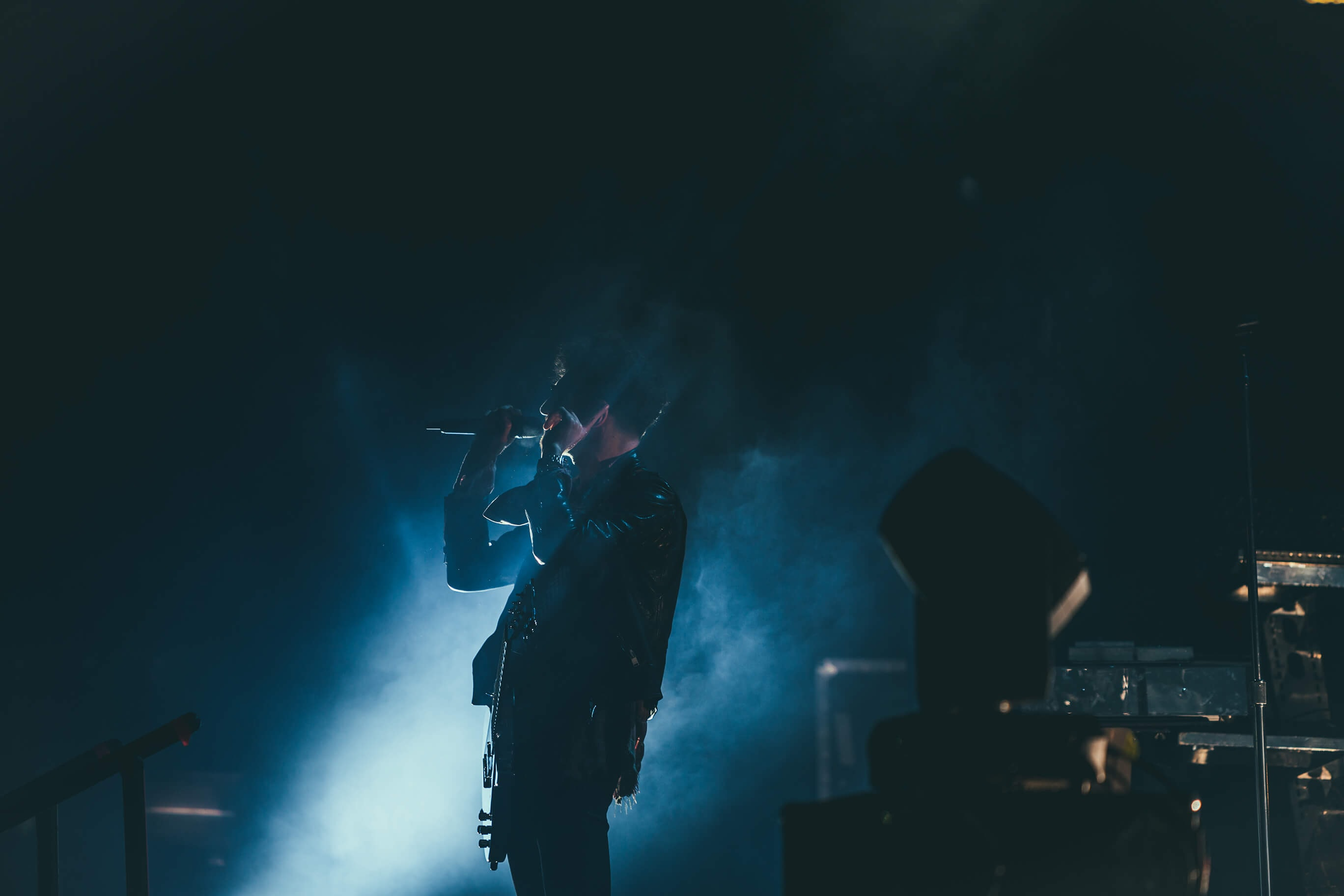 A dim shot of a musician with a microphone on stage engulfed in bluish smoke