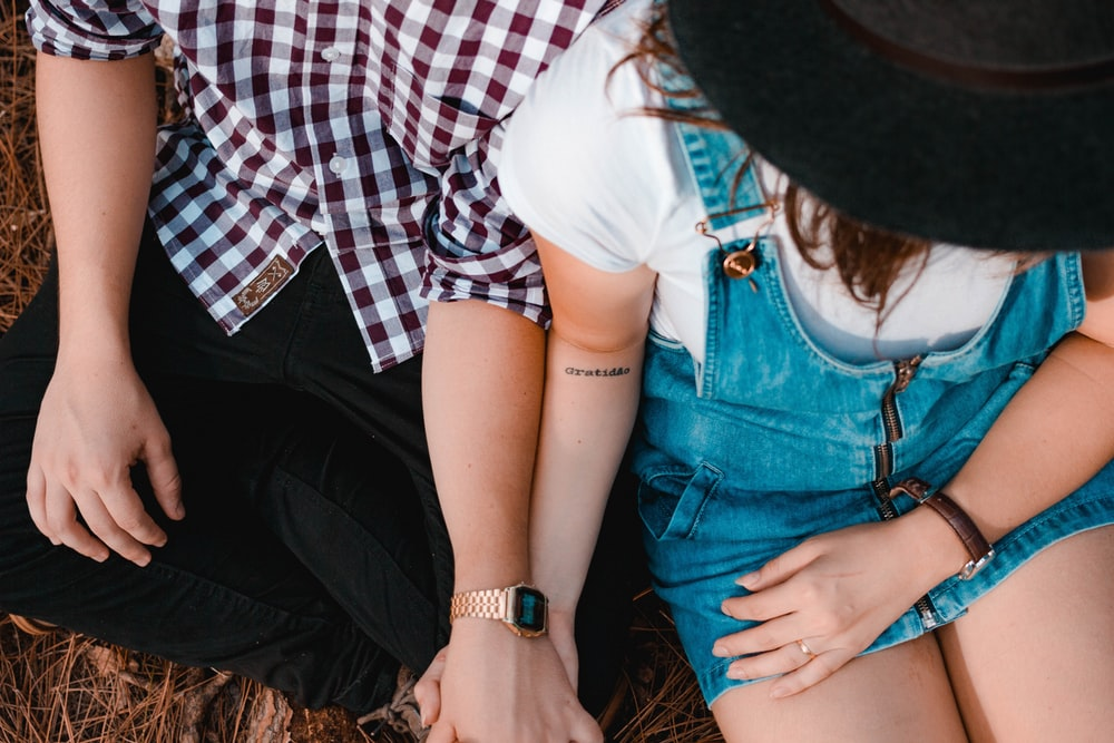 couple holding hands while sitting