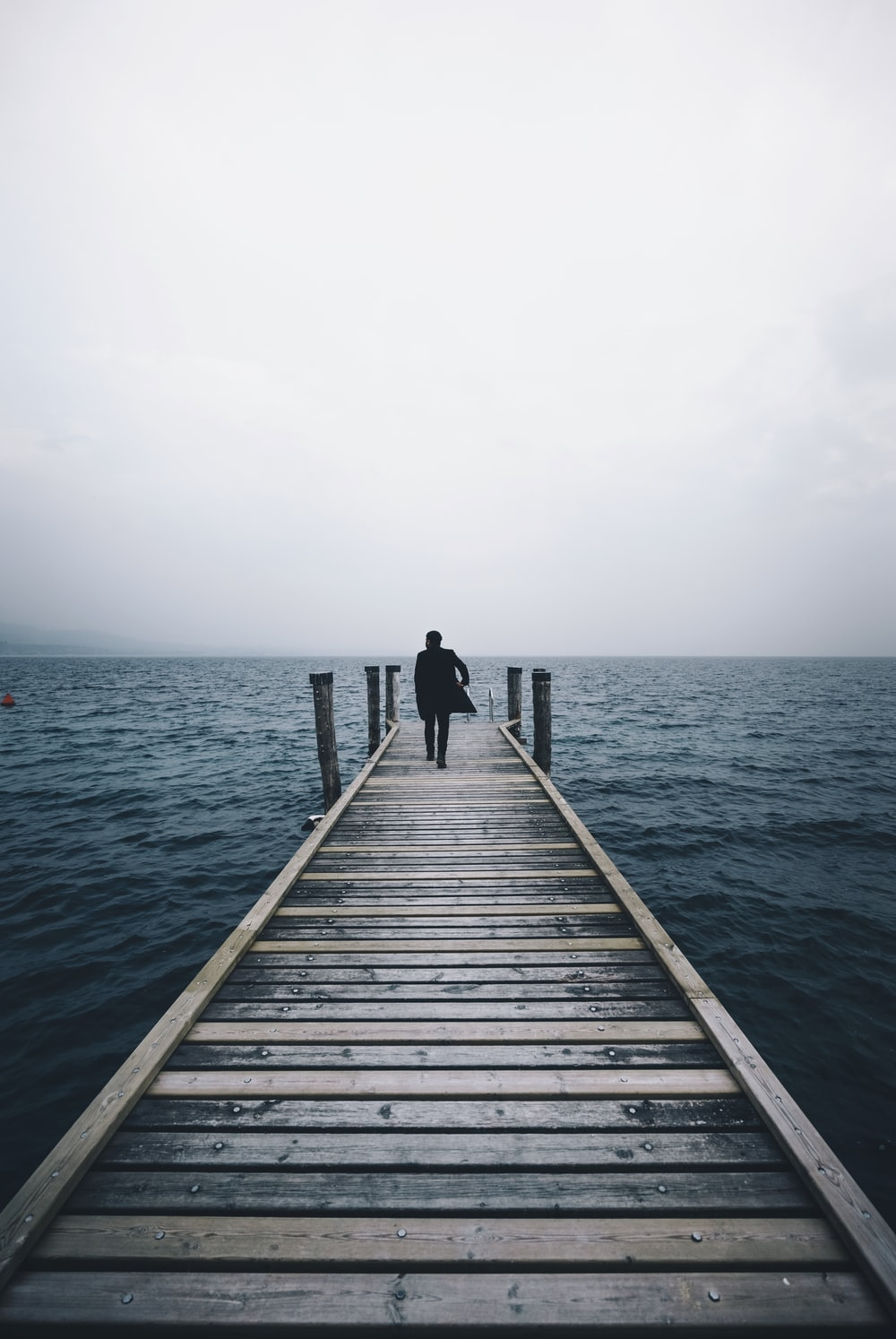 man walking on dock surrounded by ocean during daytime
