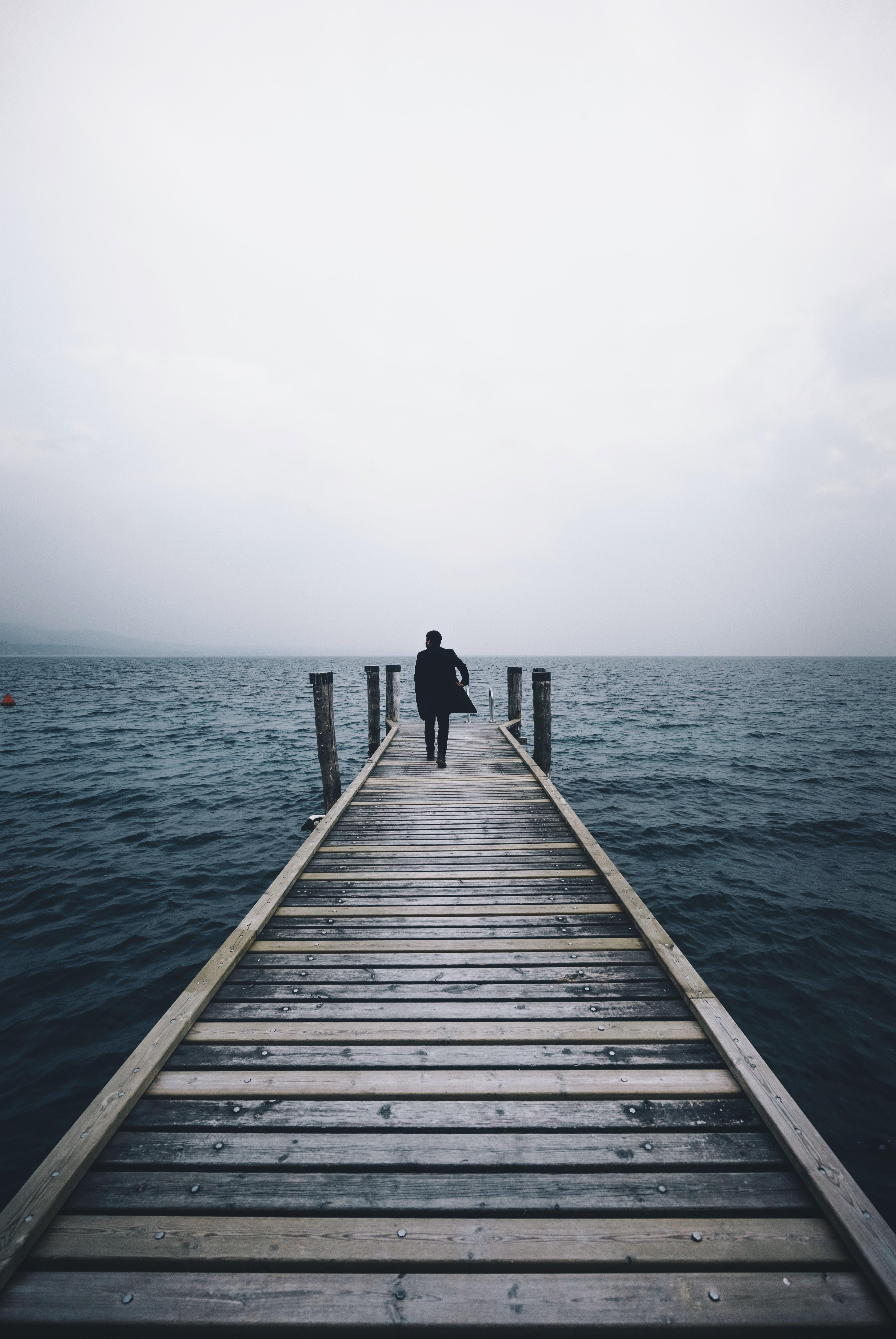 Person walks on pier on a misty morning near the ocean