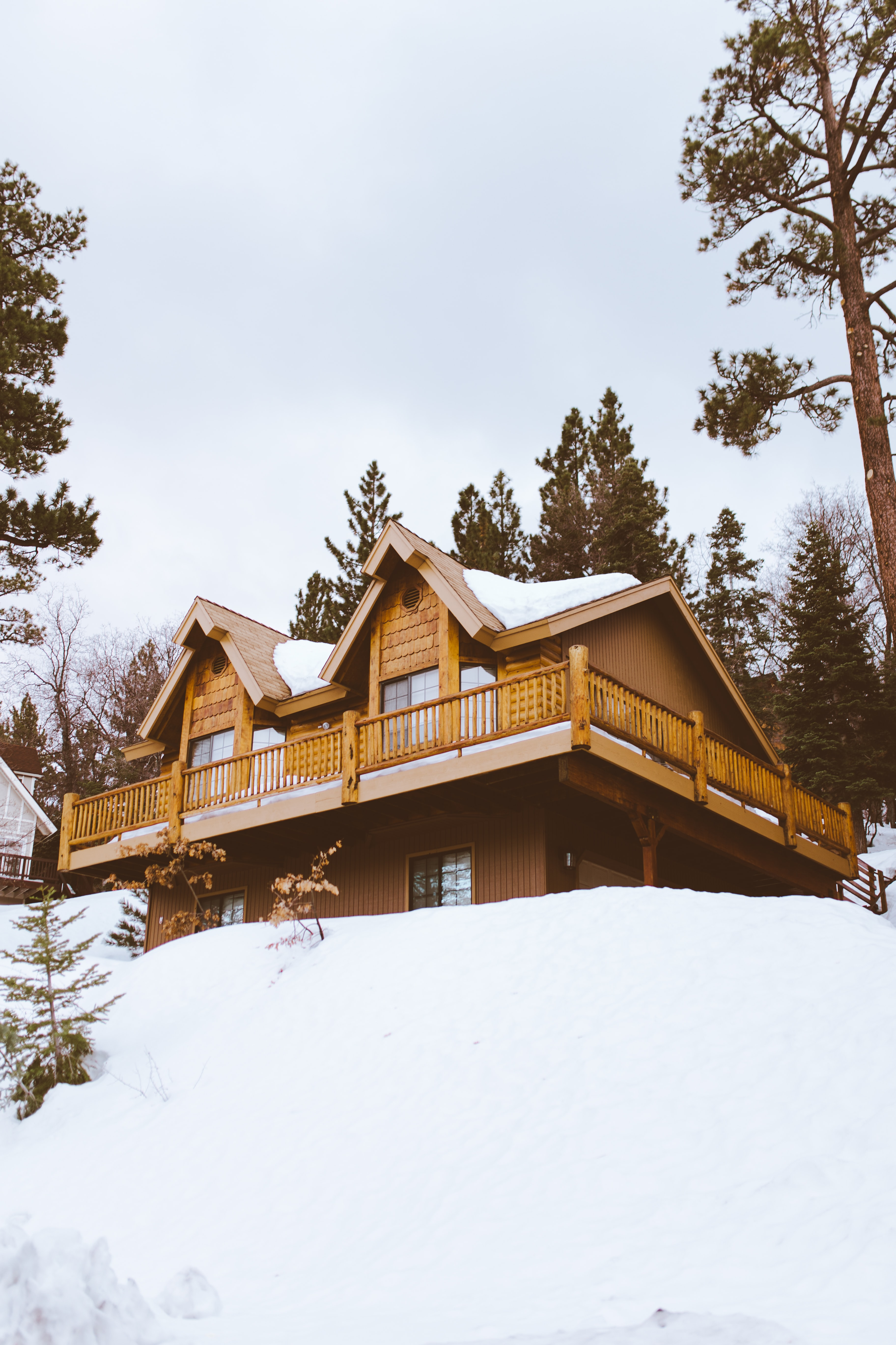 A large outdoor cabin with a wrapped deck at Big Bear Mountain Resort in California