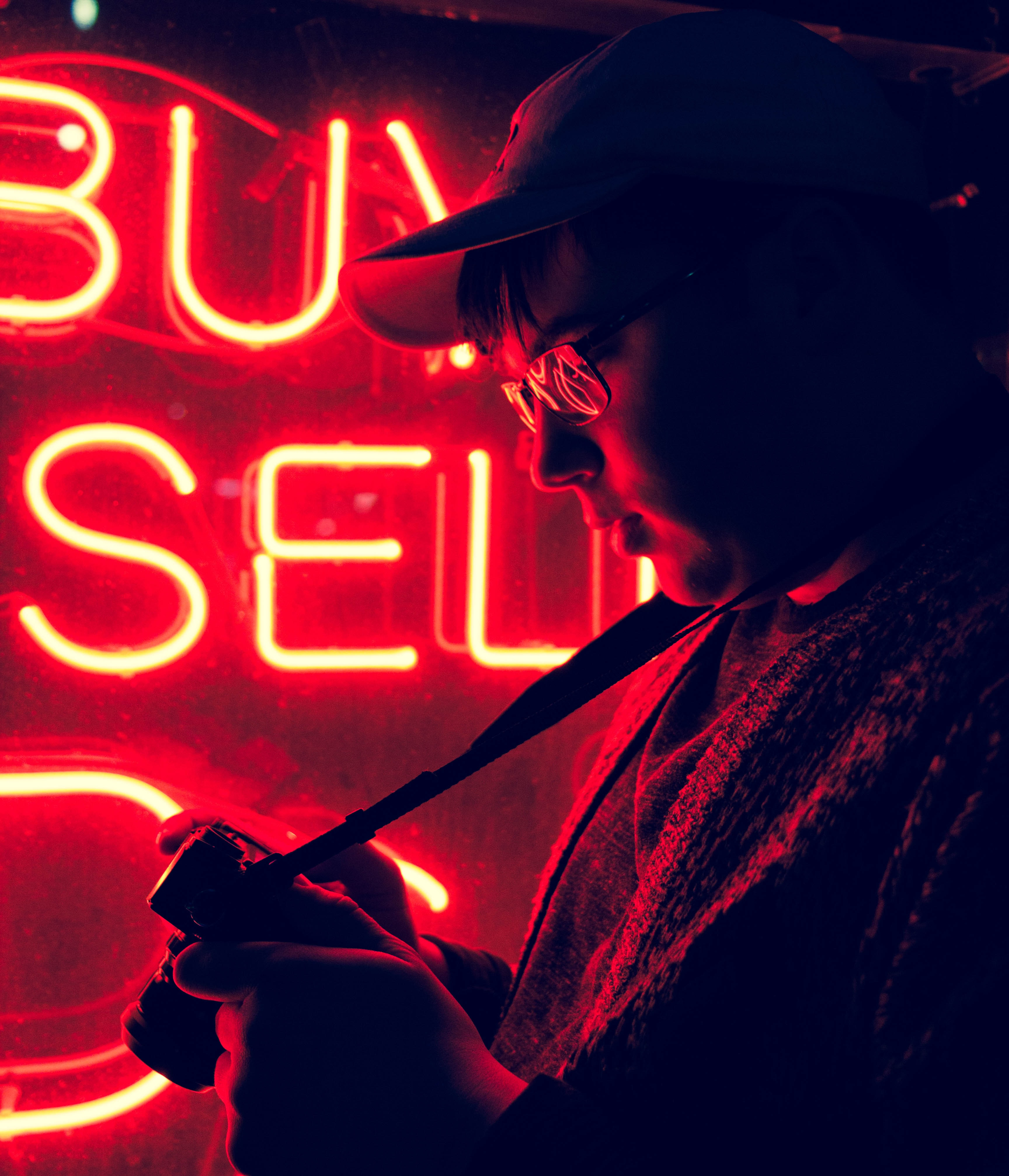 A man in glasses looking at his camera while standing near a red neon