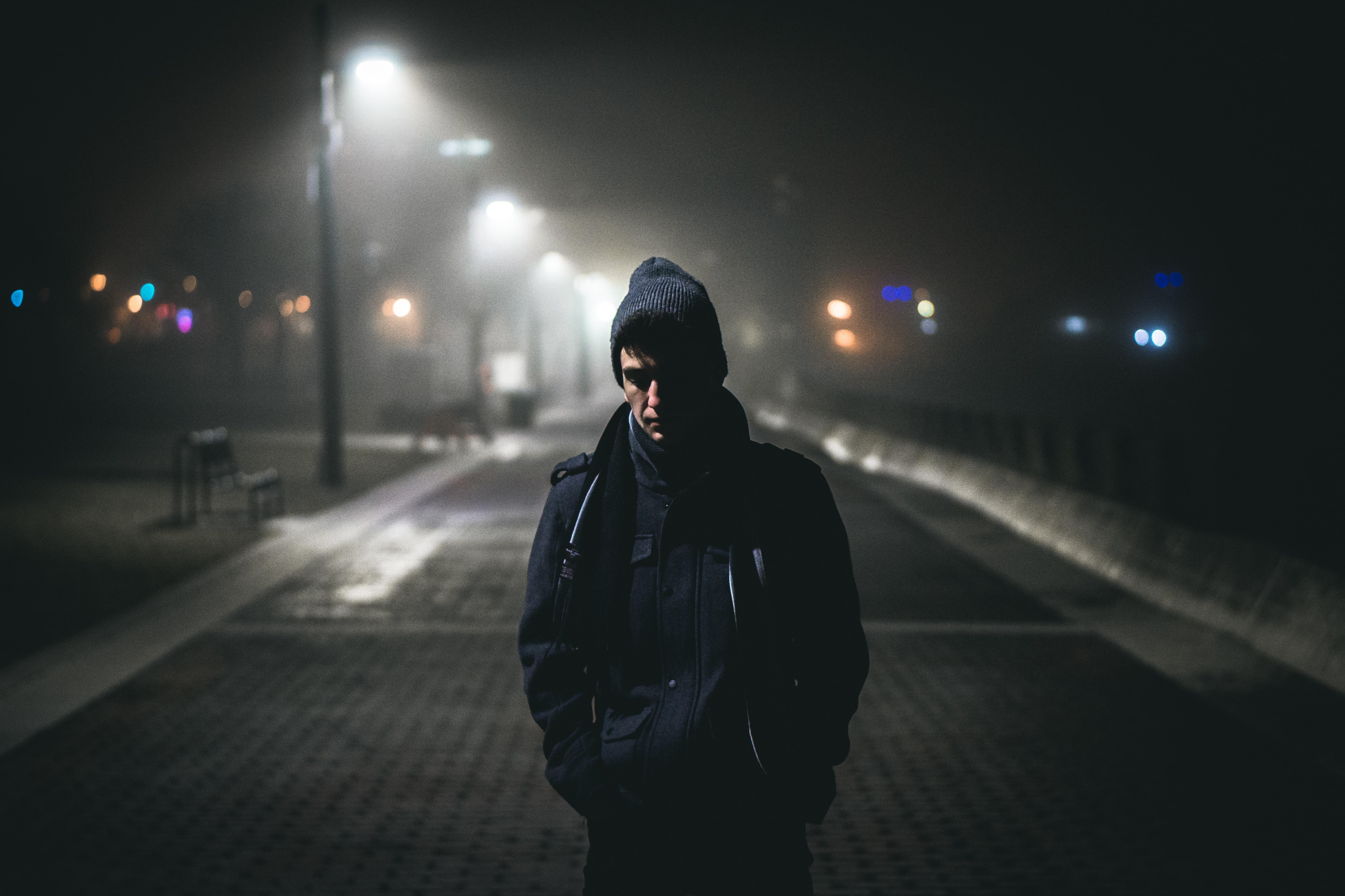man standing near street lights