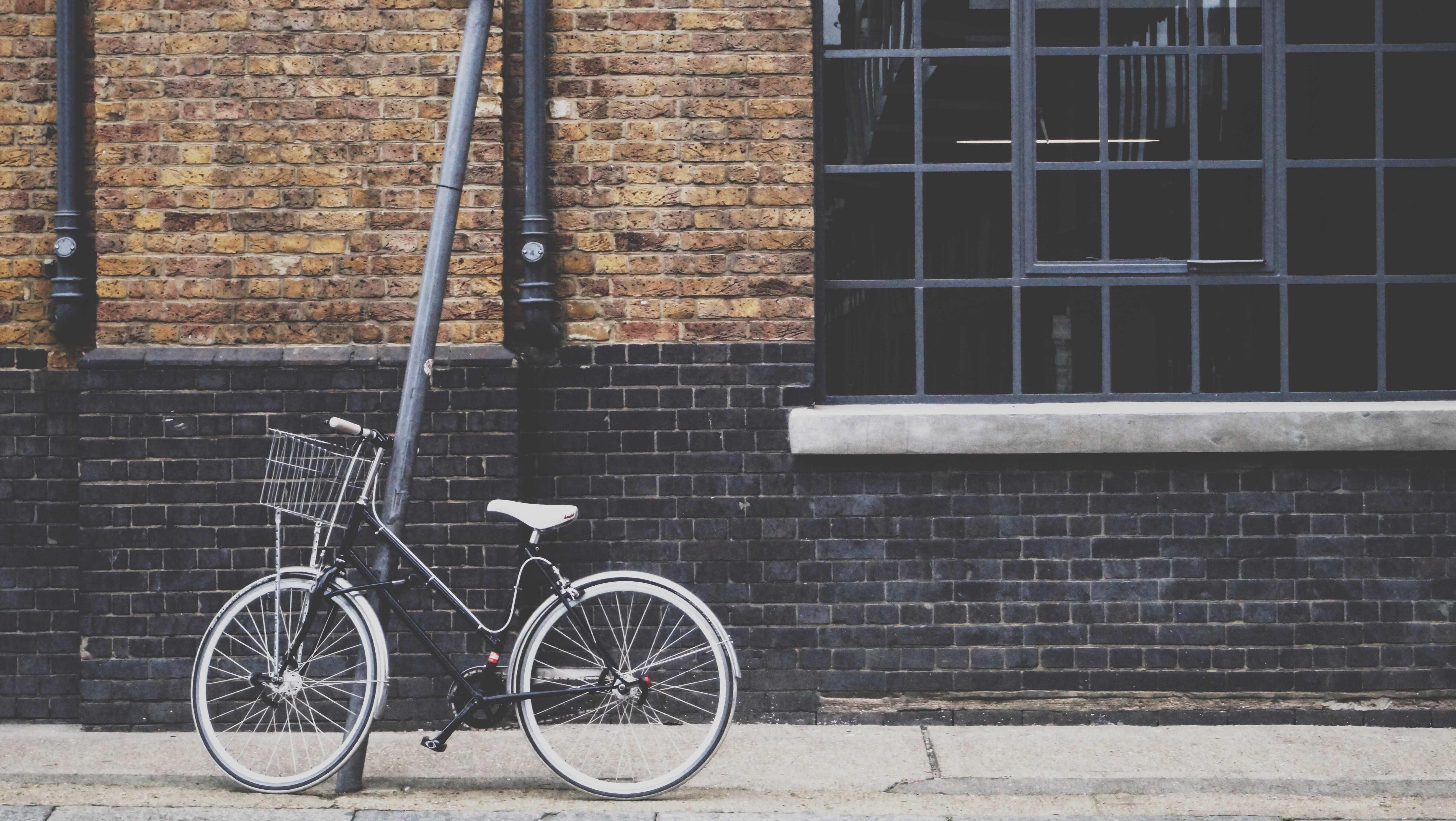 An old bicycle leans against a pole in front of a brick wall in London.
