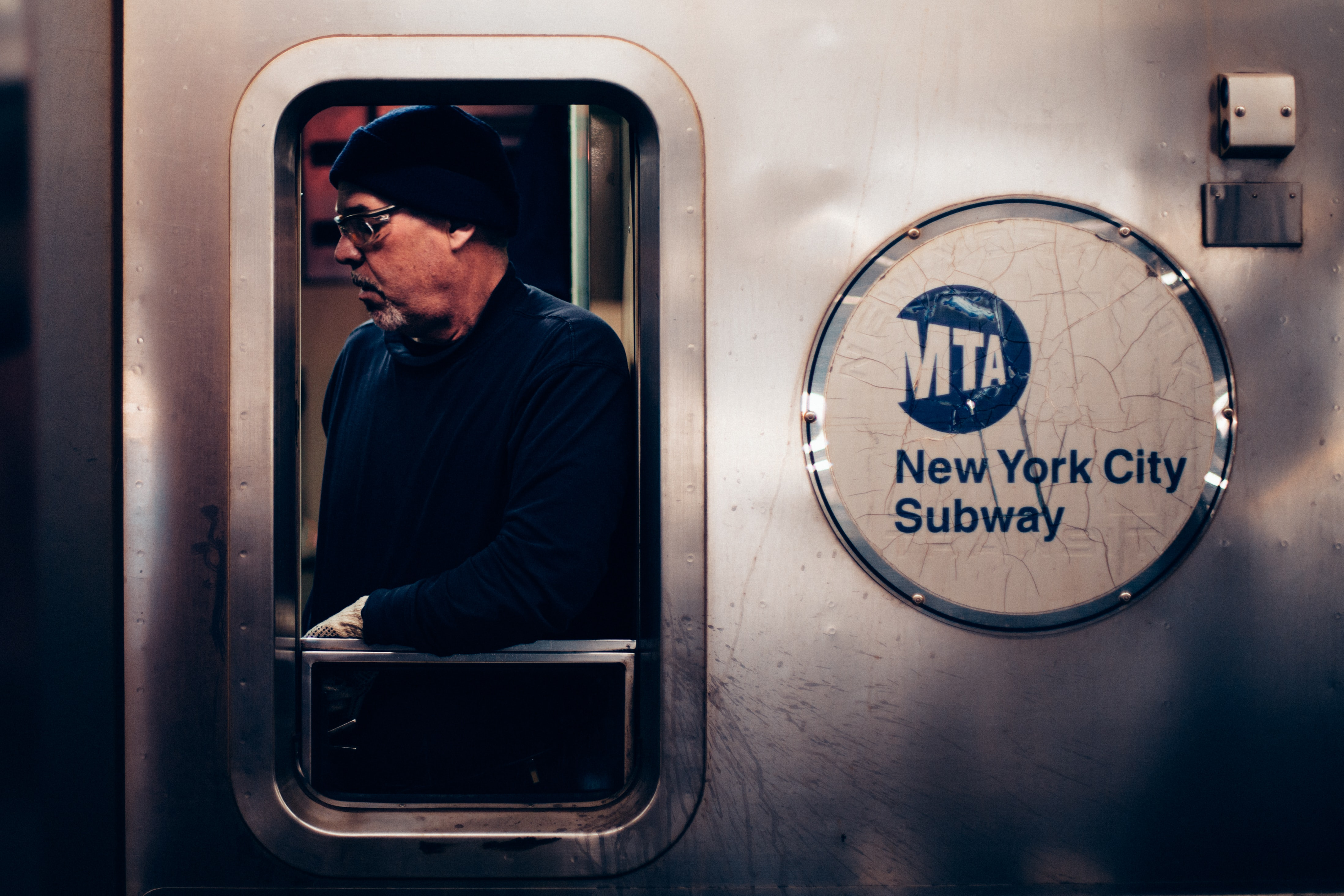 A middle-aged man in glasses and a beanie seen through a window of a subway train