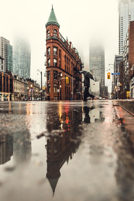 man using umbrella crossing the street during daytime