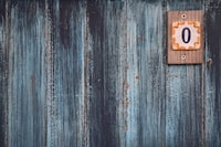 A weathered wooden wall with a small plaque with the number zero