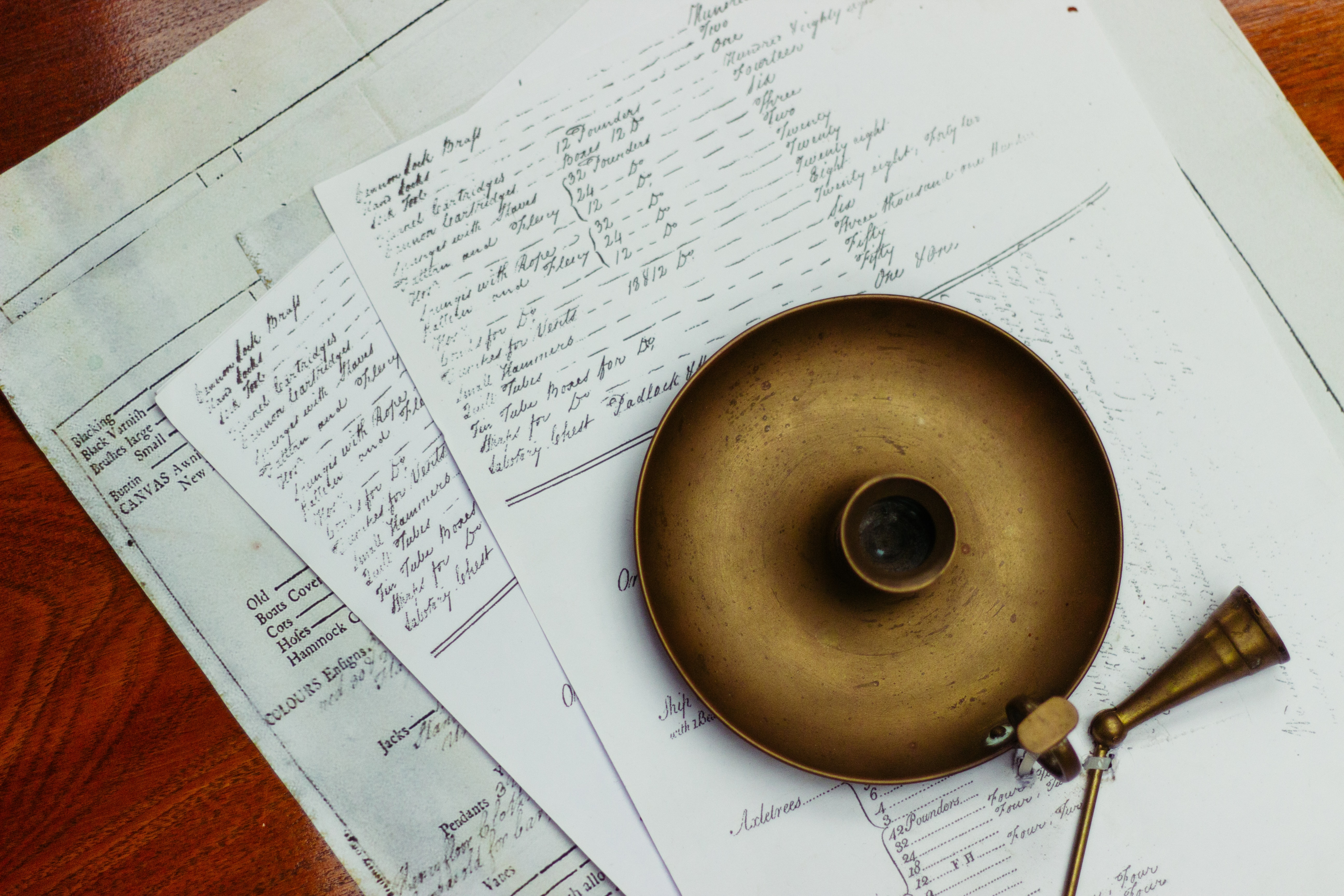An old vintage candleholder on top of papers filled with handwritten notes in Portsmouth, England, United Kingdom