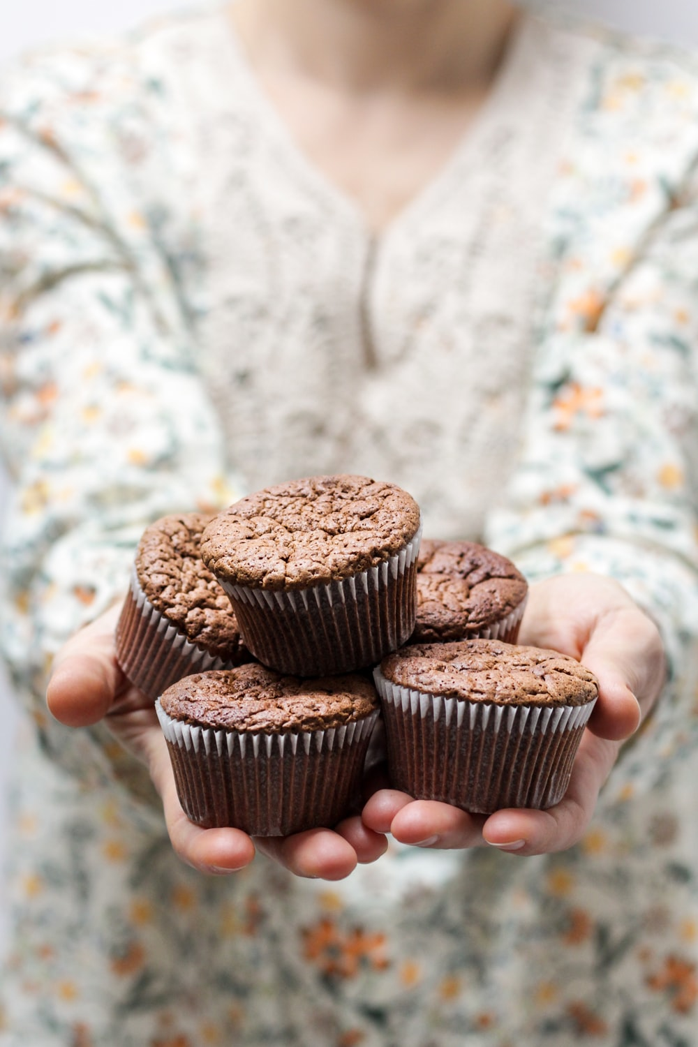 shallow focus photography of person holding 5 cupcakes